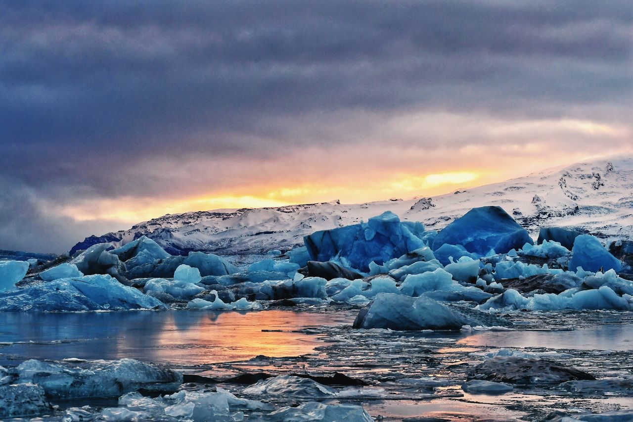 Frozen Sea Against Dramatic Sky During Sunset