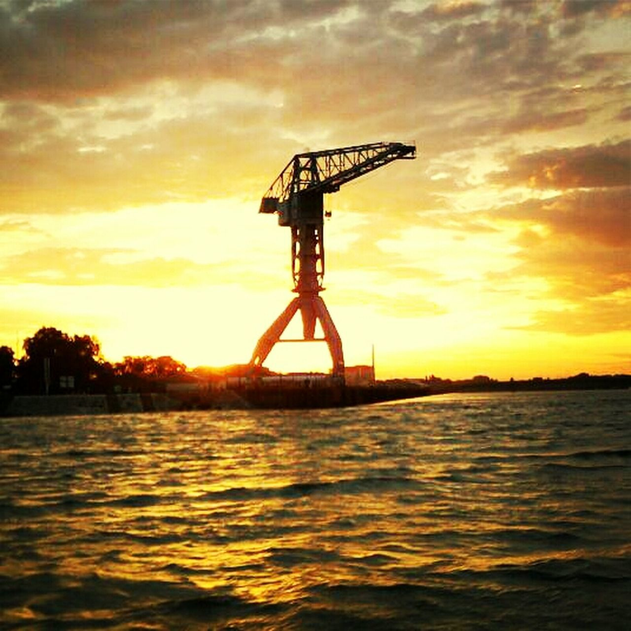 sunset, sky, silhouette, waterfront, water, nature, orange color, scenics, cloud - sky, sea, outdoors, tranquility, beauty in nature, tranquil scene, no people, offshore platform, horizon over water, drilling rig, day