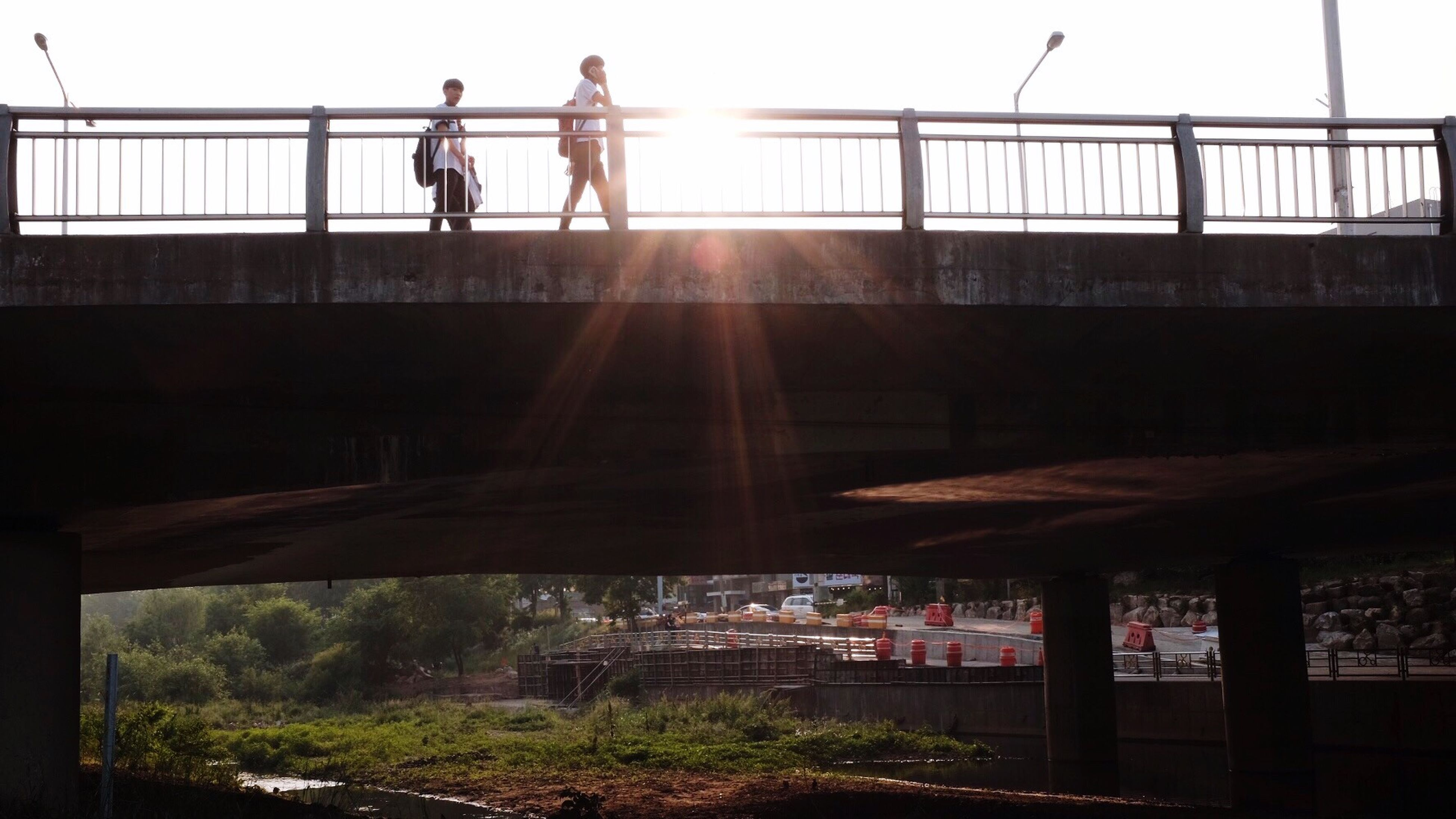 men, built structure, architecture, lifestyles, railing, sunlight, leisure activity, building exterior, person, fence, silhouette, walking, clear sky, standing, sun, sunbeam, day