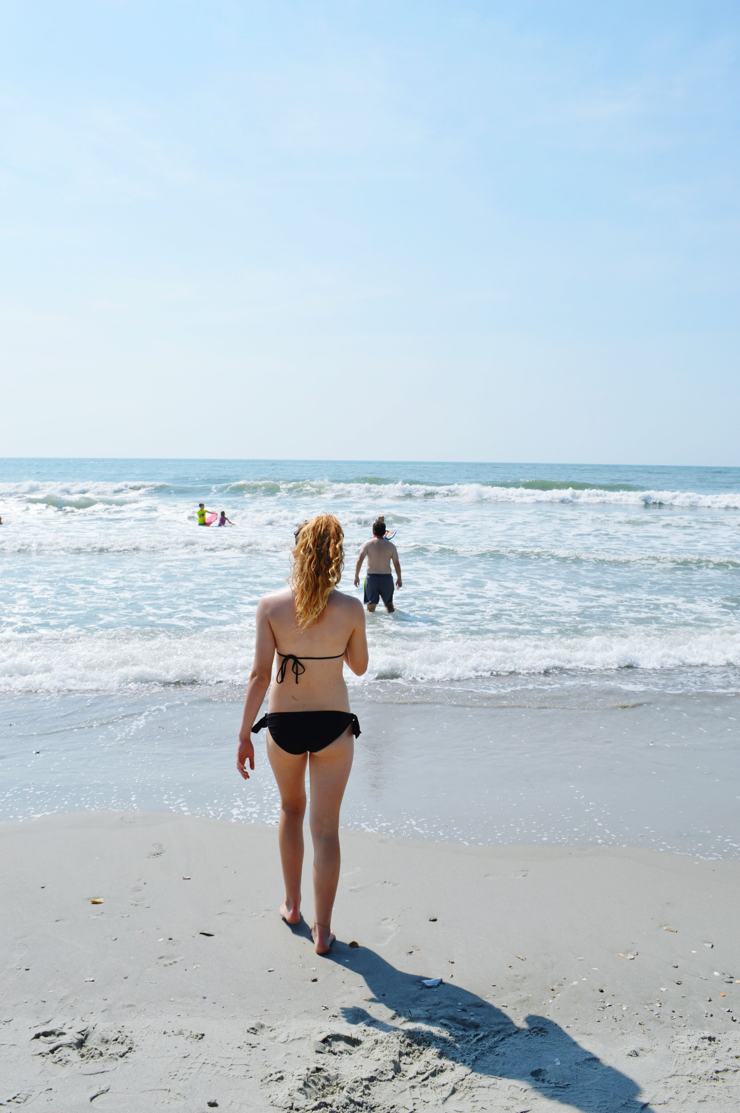 sea, beach, horizon over water, water, leisure activity, shore, lifestyles, sand, vacations, full length, rear view, togetherness, clear sky, person, sky, casual clothing, enjoyment, weekend activities, summer
