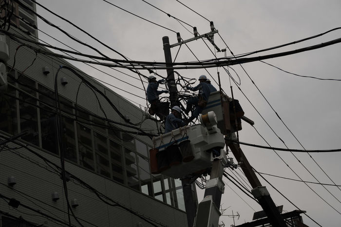 Built Structure Cable Connection Day Electricity  Fujifilm FUJIFILM X-T2 Fujifilm_xseries Japan Japan Photography Low Angle View Manual Worker Men Occupation Outdoors Power Line  Power Supply Real People Repairing Sky Working X-t2 電柱 電線 高所恐怖症