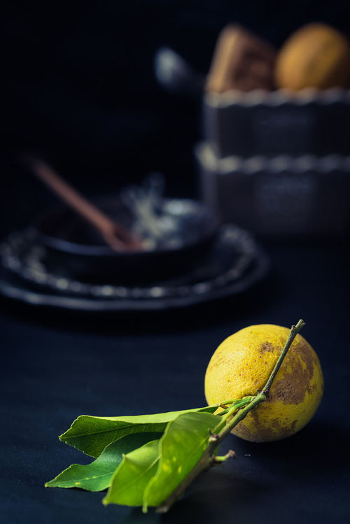 organic lemon with leaves in the foreground; kitchenware blurred on dark background Battered Batteredfood Black Blue Branches And Leaves Chiaroscuro  Citrus  Close Up Darkness And Light Food Freshness Fruit Healthy Eating Juice Juicy Fruit Lemon Melancholy Moody No People Organic Food Sad Silvery Silvery Things Vitamin Yellow Color