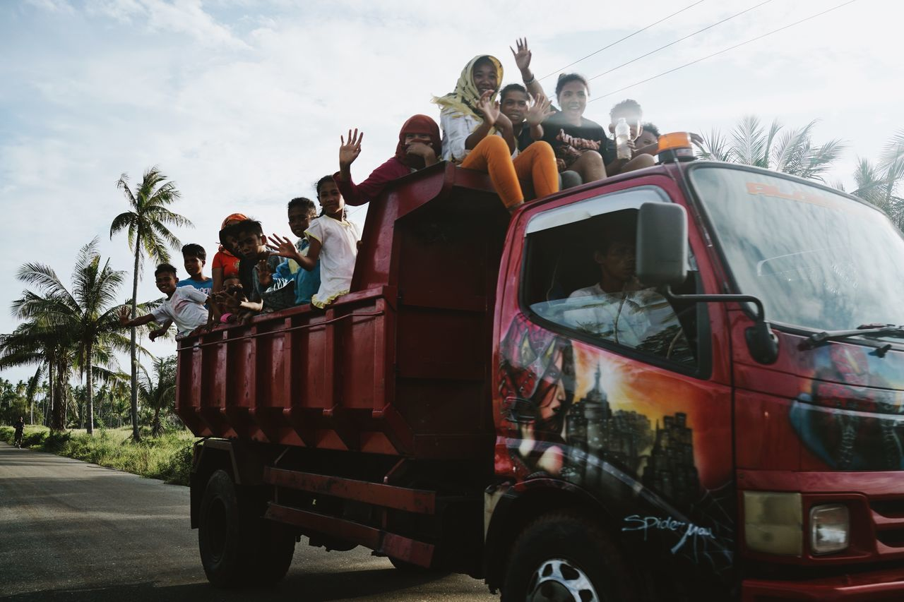 ASIA Children Daily Life Day Driving Driving By Happy INDONESIA Kids Maluku  Moluccas Morotaiisland On The Road Painted Trucks Palm Trees People Red Truck Snapshot Sunny Day Transportation Travel Truck Vehicle Waving The Photojournalist - 2017 EyeEm Awards The Street Photographer - 2017 EyeEm Awards
