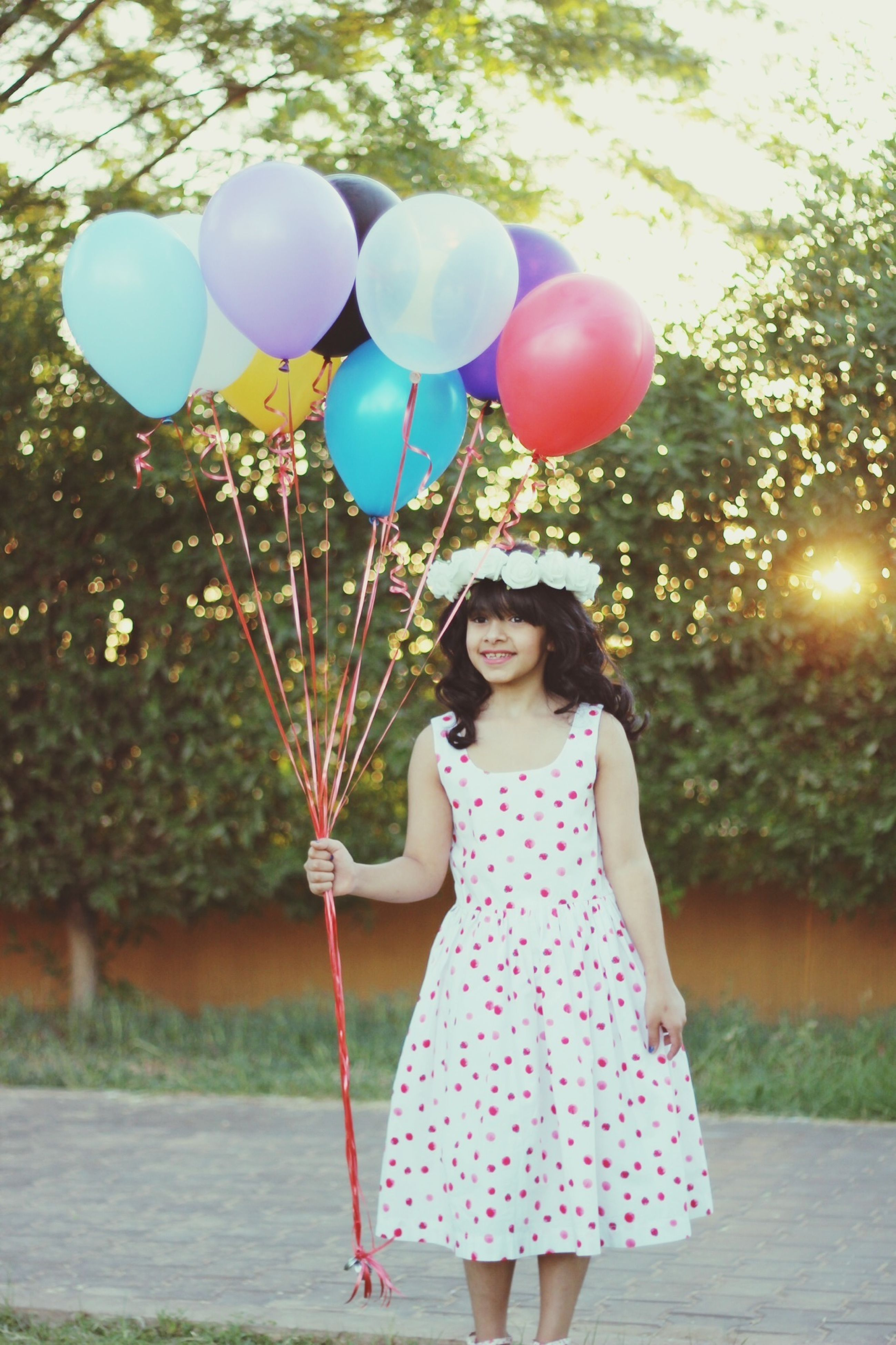 hanging, tree, celebration, decoration, low angle view, branch, lighting equipment, sunlight, outdoors, childhood, close-up, day, growth, balloon, swing, lens flare, focus on foreground, tradition, nature, christmas