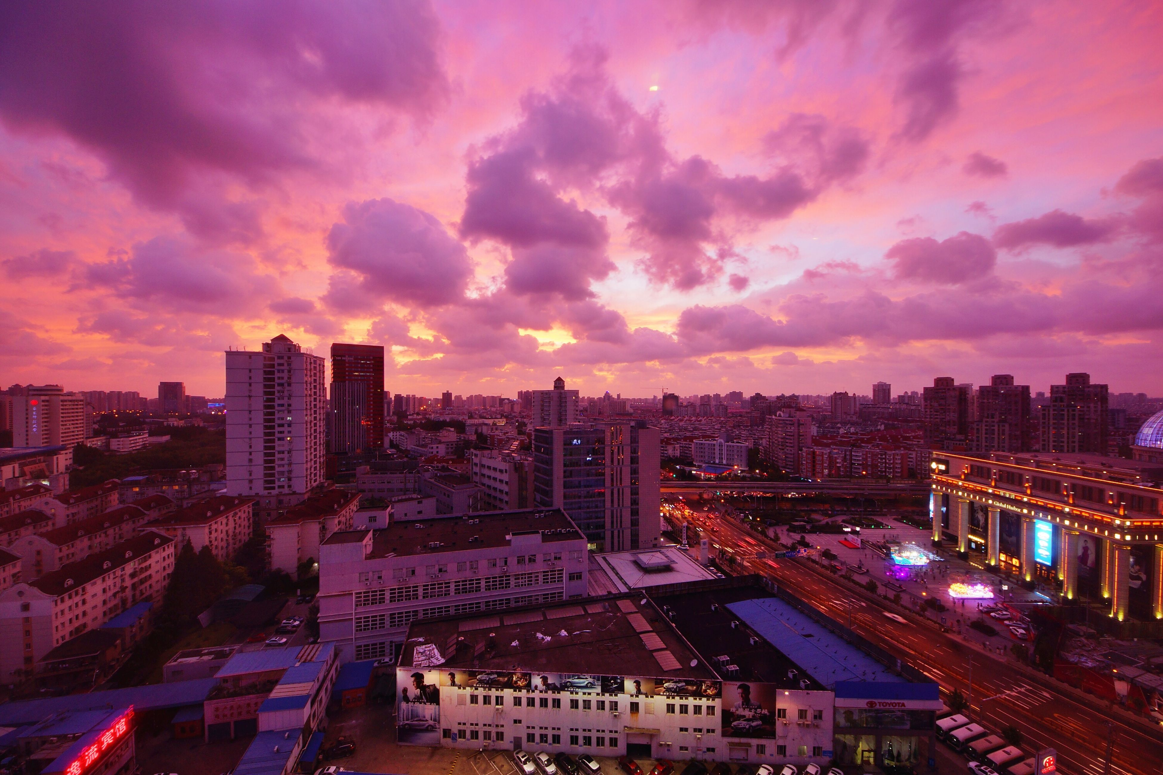 city, building exterior, architecture, built structure, cityscape, sunset, sky, cloud - sky, high angle view, illuminated, city life, dusk, orange color, cloudy, residential building, residential district, car, cloud, skyscraper, road