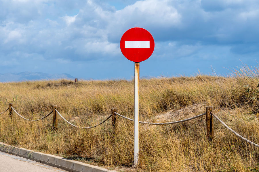 Grass No Entry Sign Beauty In Nature Cloud - Sky Communication Day Field Grass Guidance Landscape Nature No People Outdoors Red Road Road Sign Sky Son Serra De Marina Traffic Sign