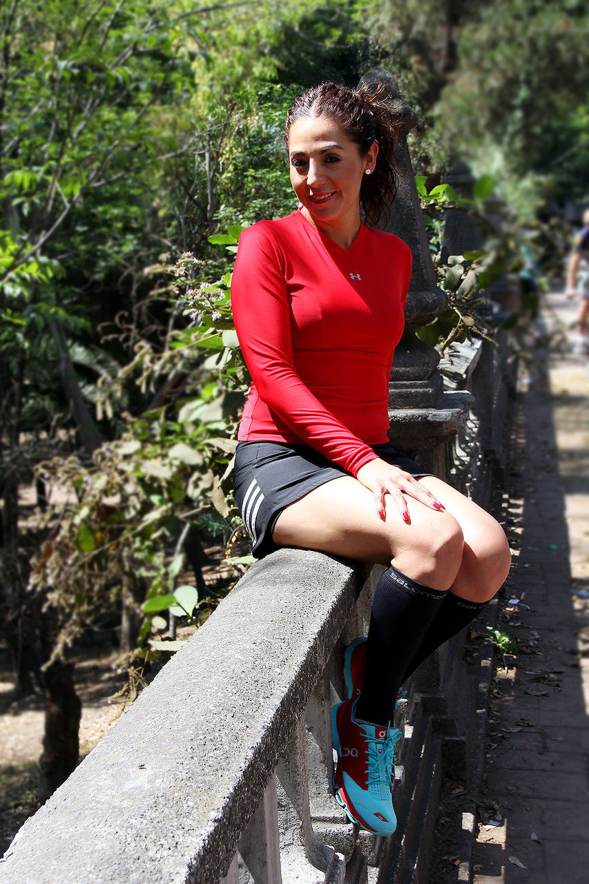 real people, young adult, young women, one person, leisure activity, lifestyles, casual clothing, full length, day, outdoors, looking at camera, sitting, smiling, happiness, tree, beautiful woman, retaining wall, portrait, nature
