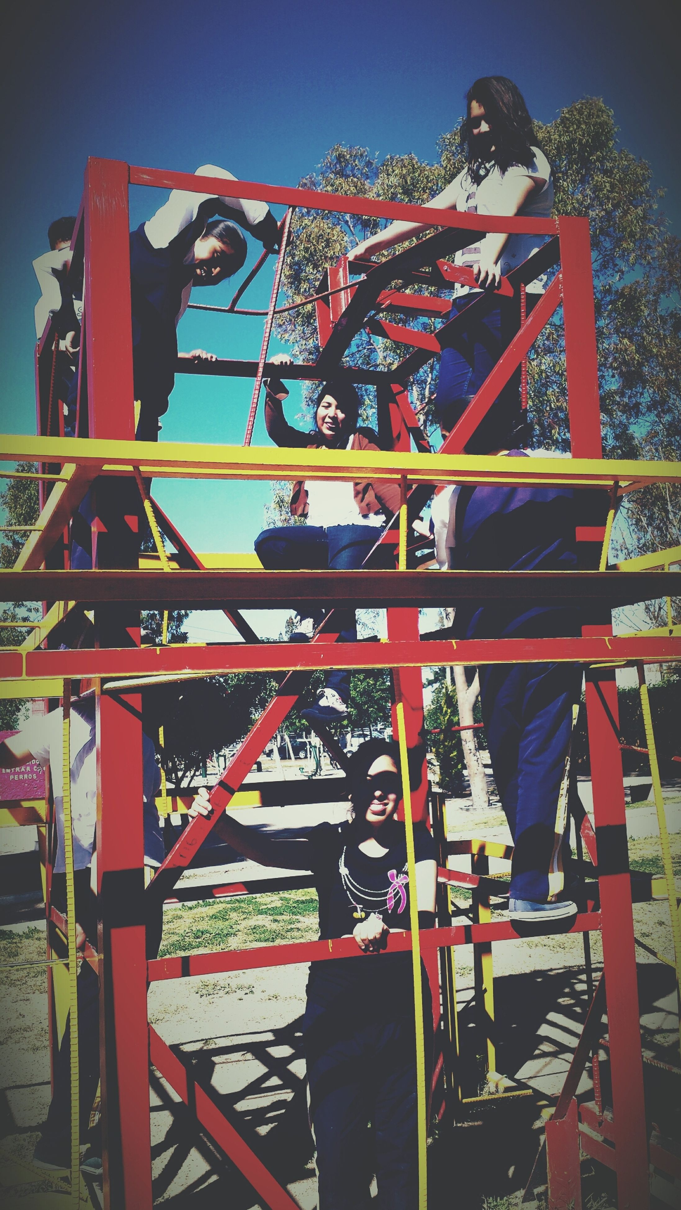 leisure activity, lifestyles, low angle view, red, amusement park, metal, standing, childhood, arts culture and entertainment, casual clothing, sky, built structure, men, amusement park ride, boys, fun, enjoyment, protection