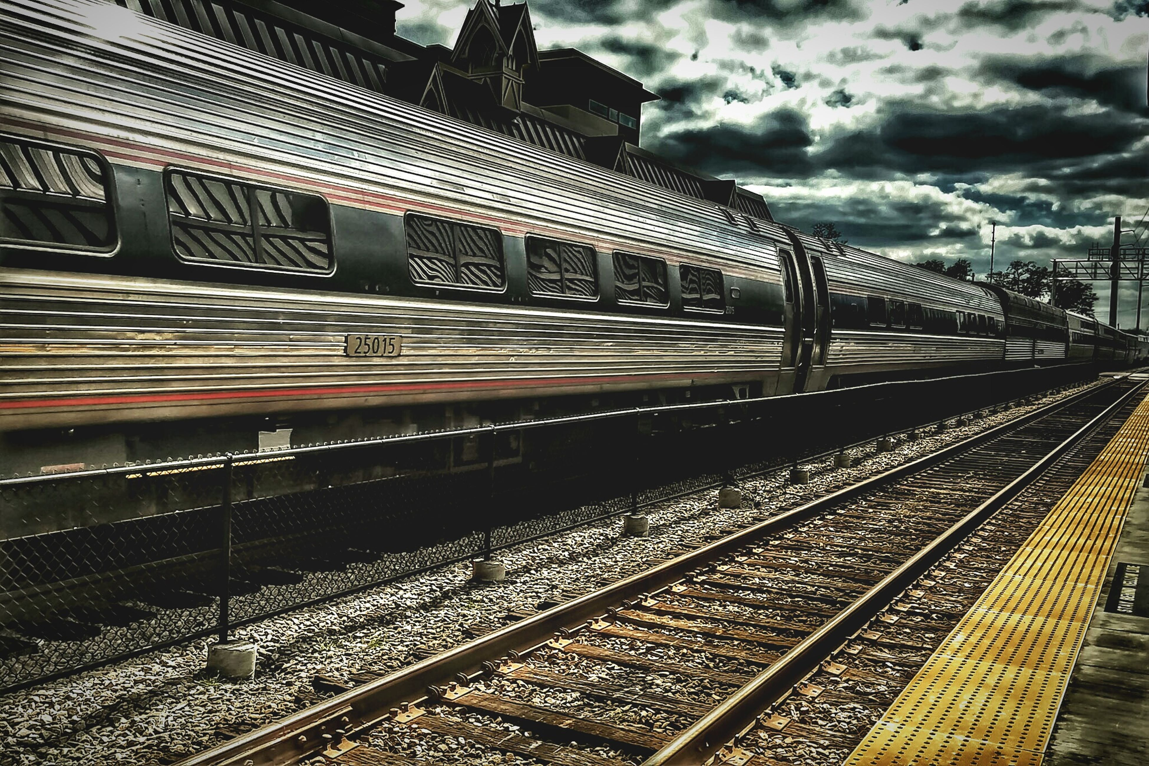 railroad track, rail transportation, sky, architecture, built structure, cloud - sky, railroad station, transportation, low angle view, railroad station platform, public transportation, cloudy, railing, building exterior, no people, steps, the way forward, metal, cloud, day