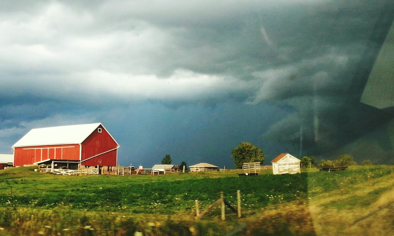 Exterior Of Barn On Field Against Cloudy Sky