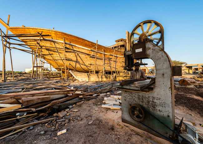 boat building in Persian Gulf Blue Boat Builder Boat Building Built Structure Clear Sky Machinery Mode Of Transport Outdoors Sunlight Wooden Boat Wooden Boat Skeleton