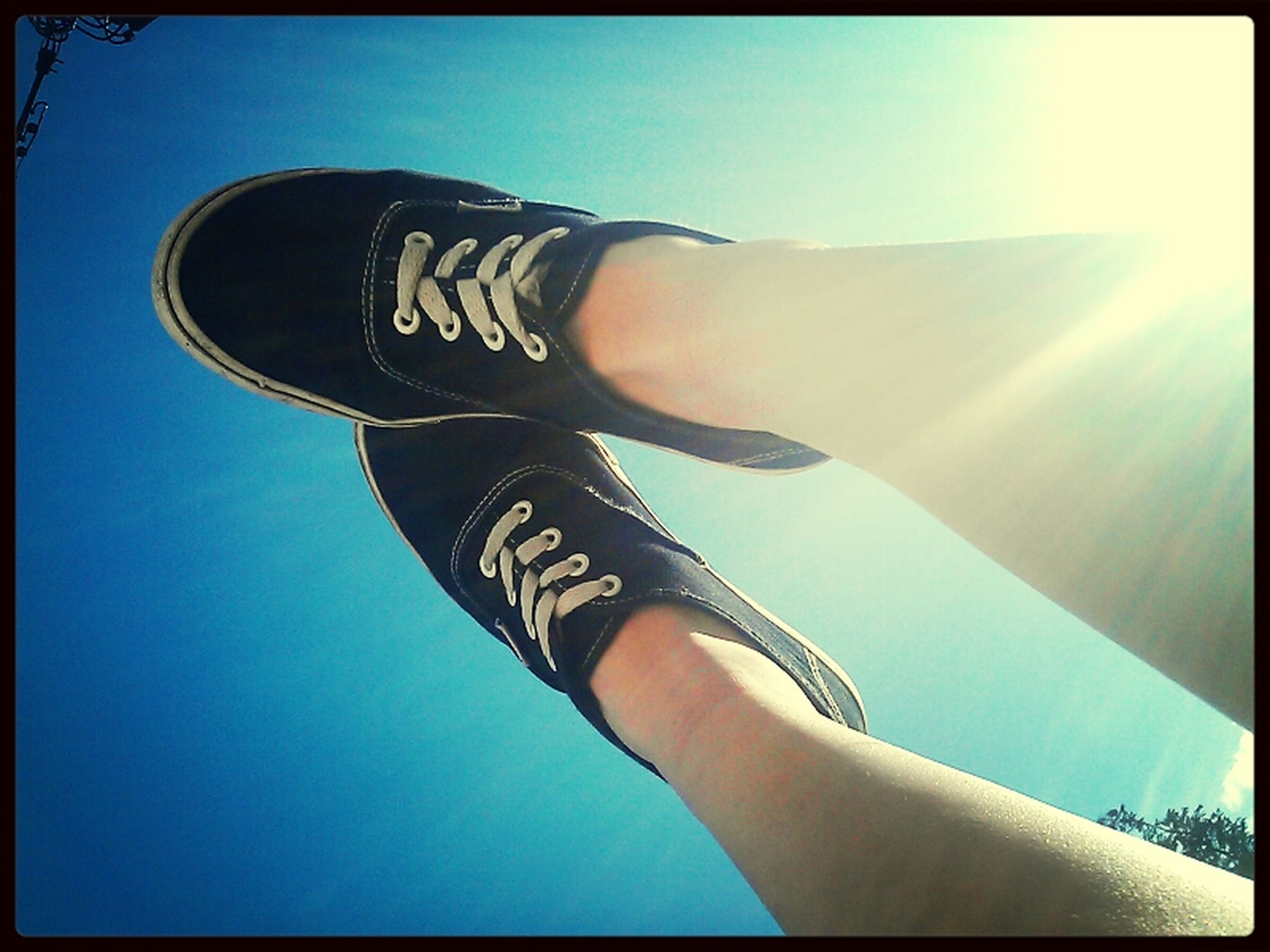 low section, person, sunlight, personal perspective, lifestyles, transfer print, blue, sky, part of, auto post production filter, leisure activity, sunny, legs crossed at ankle, low angle view, day, sun