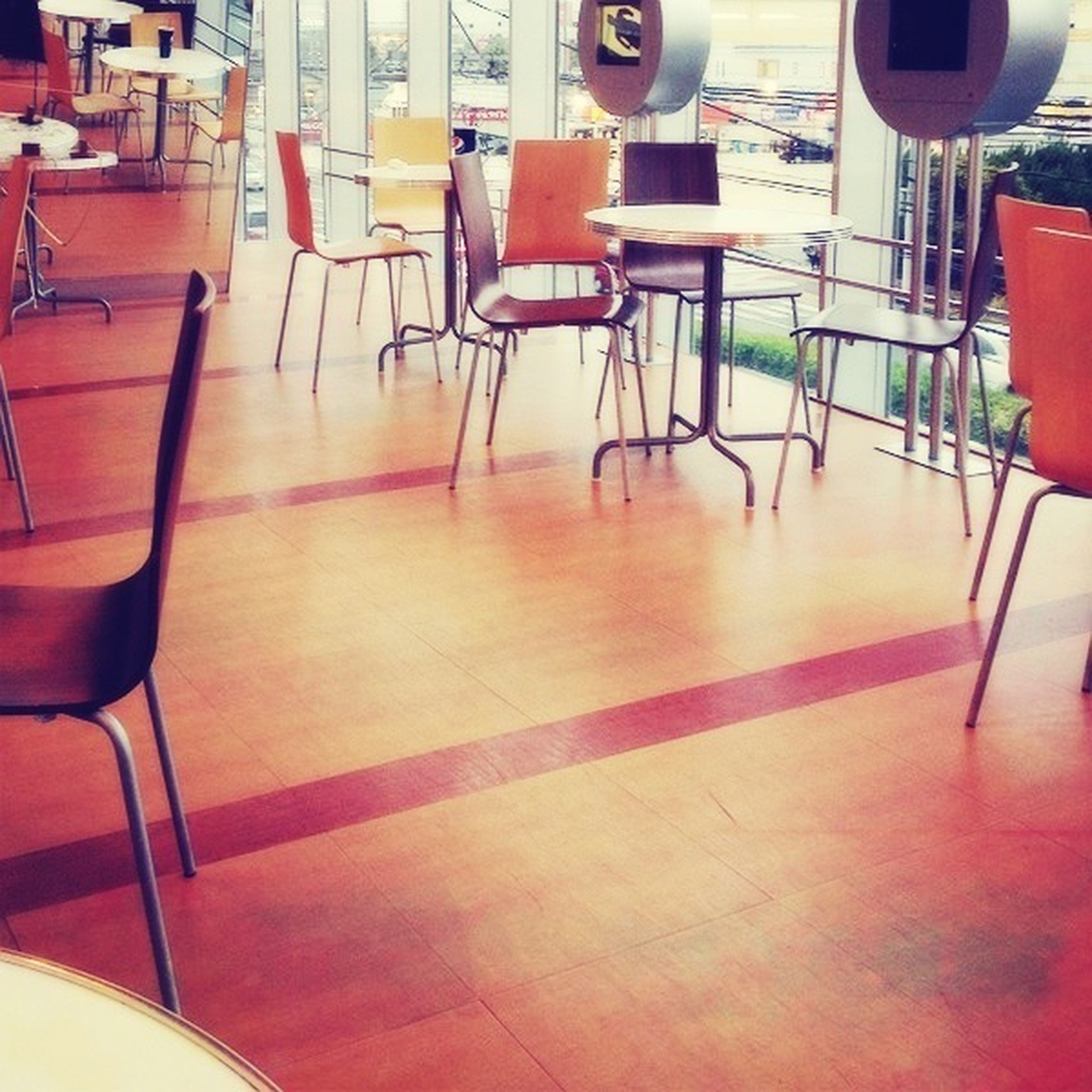 chair, empty, absence, indoors, seat, table, built structure, architecture, furniture, no people, flooring, red, day, in a row, reflection, window, tiled floor, restaurant, sunlight, building exterior