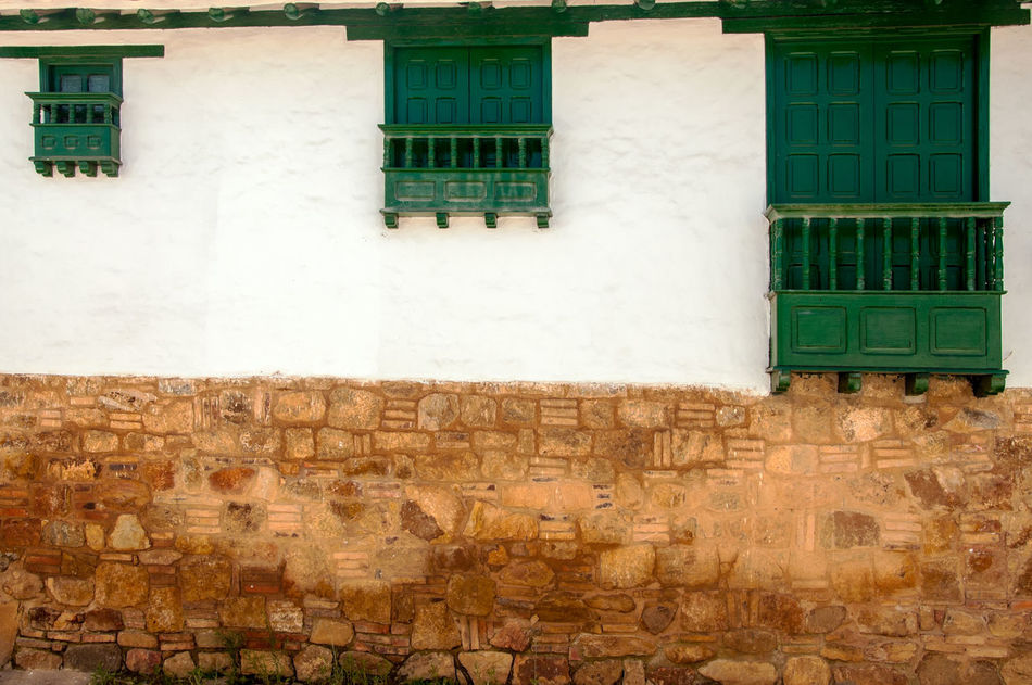 Three windows of different sizes in a colonial town. America Architecture Boyaca Building Colombia Colonial Country Countryside Exterior Historic House Latin Outdoors Residence South Stone Style Town Travel Typical VillaDeLeyva Wall White Window Wood