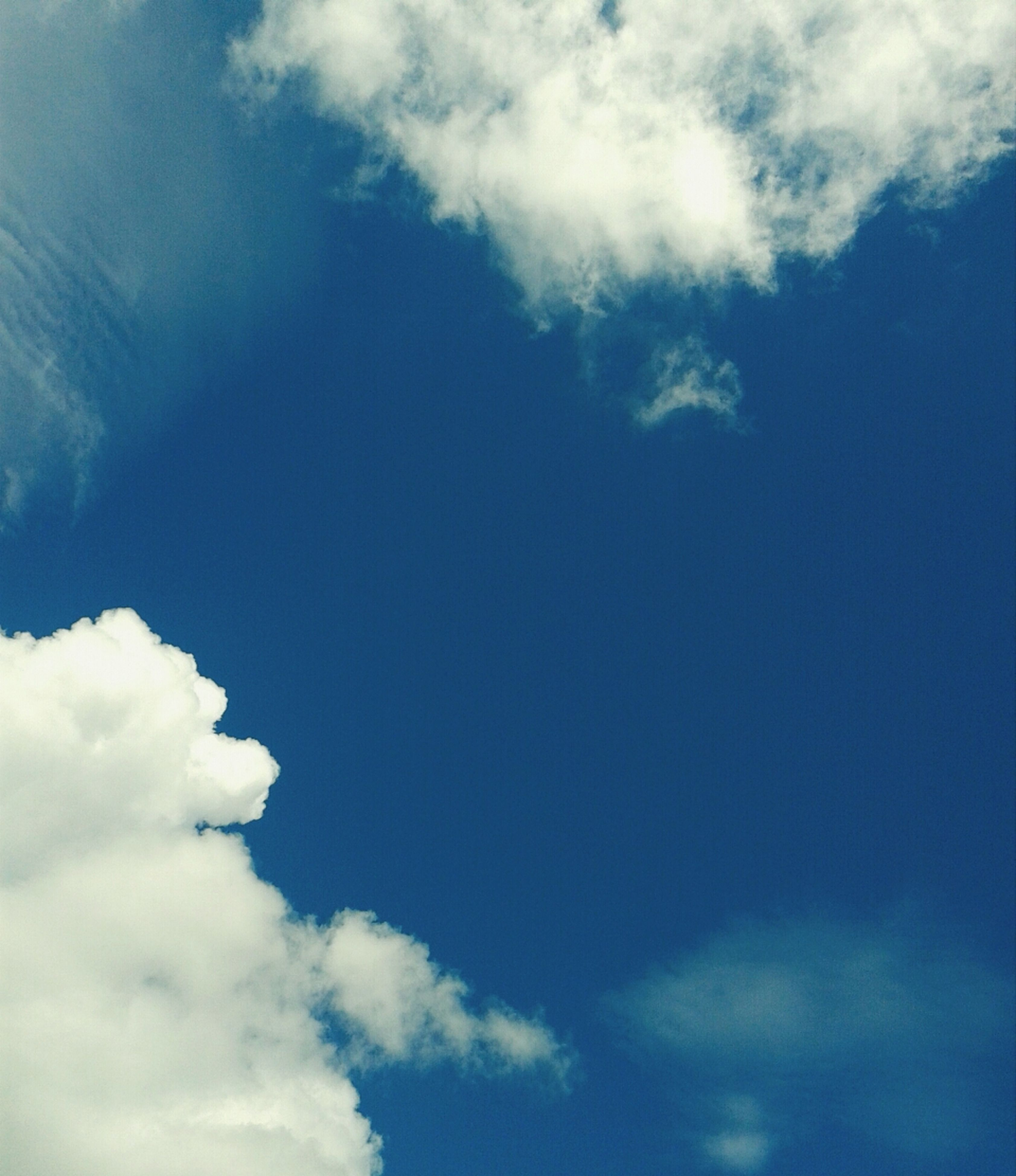 low angle view, sky, blue, cloud - sky, beauty in nature, sky only, tranquility, nature, cloud, scenics, cloudy, white color, cloudscape, tranquil scene, backgrounds, day, outdoors, no people, idyllic, full frame