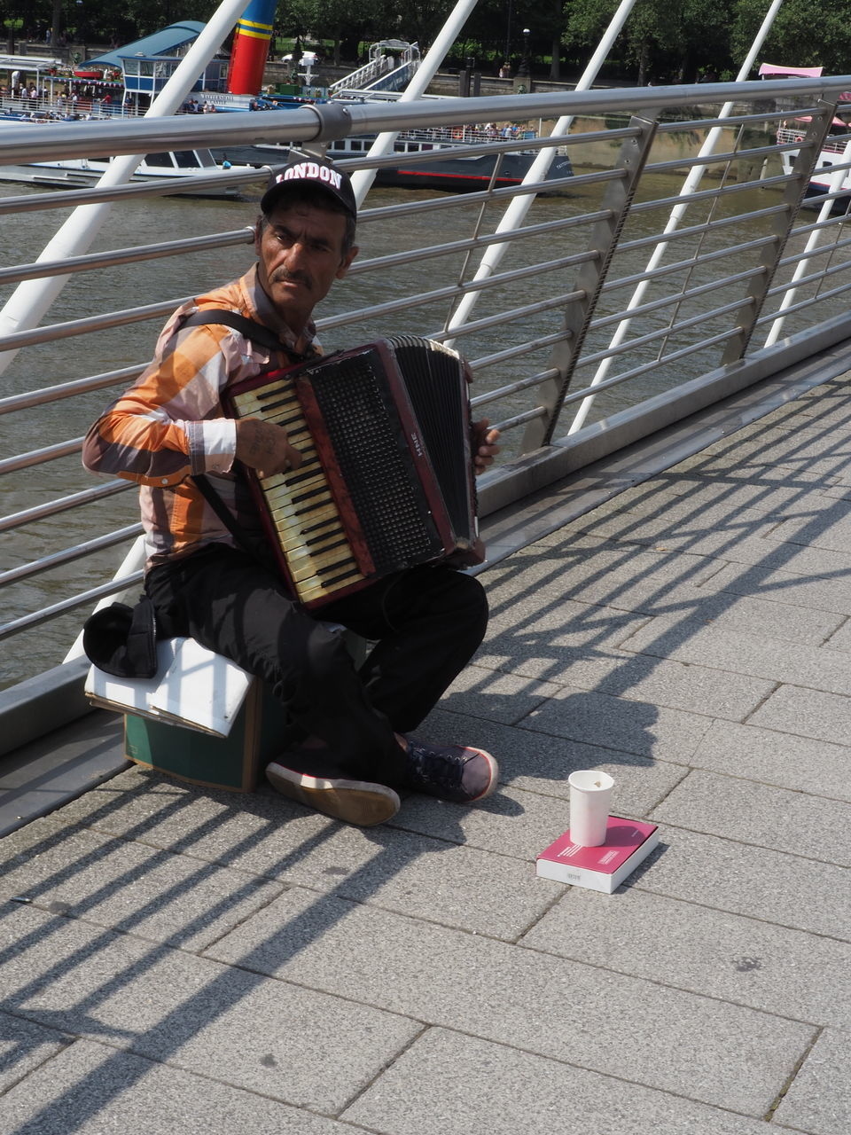 accordion, full length, real people, outdoors, one person, musical instrument, mid adult, playing, day, men, music, lifestyles, sunlight, sitting, musician, one man only, young adult, adult, adults only, people
