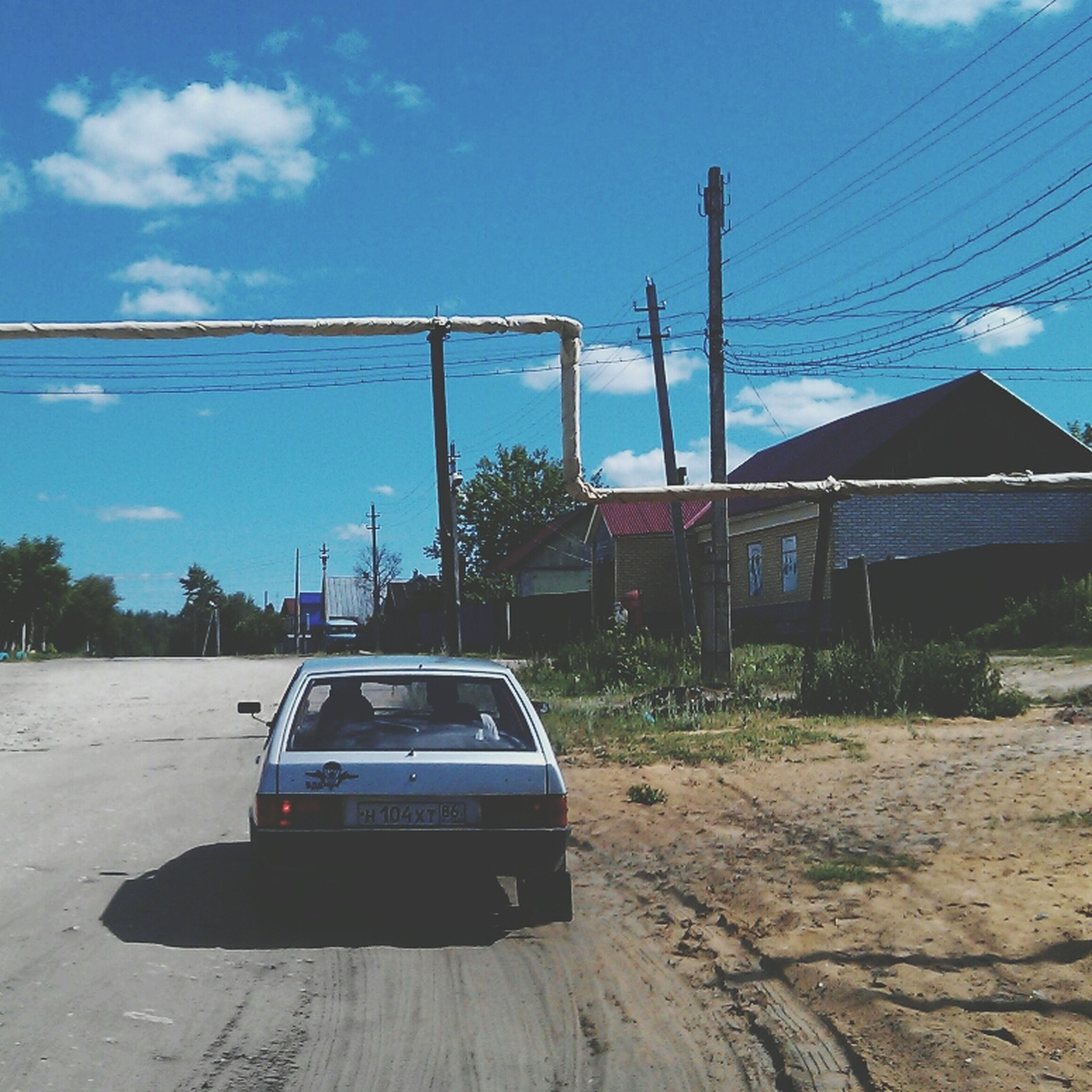 transportation, power line, sky, electricity pylon, mode of transport, blue, cable, sunlight, electricity, connection, power supply, built structure, day, outdoors, land vehicle, tree, cloud, car, no people, architecture