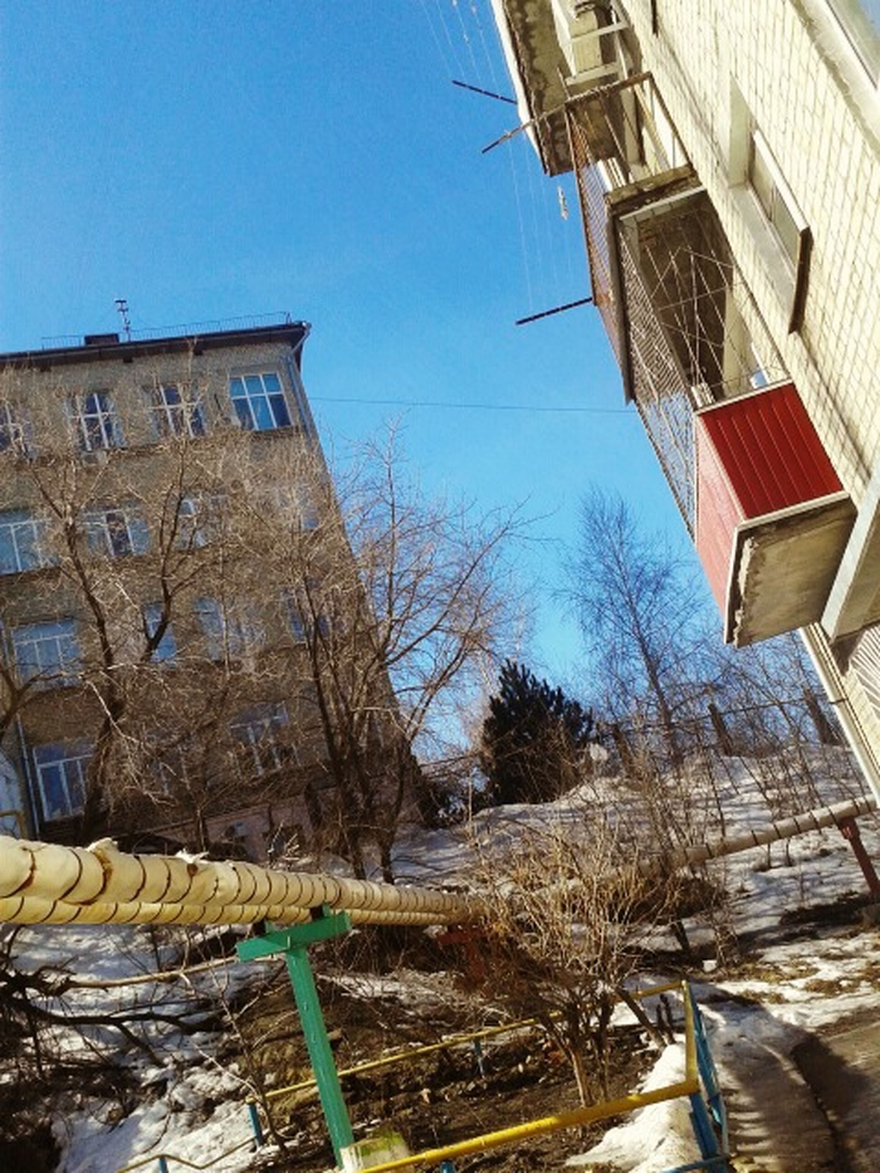 building exterior, architecture, built structure, clear sky, house, low angle view, residential structure, residential building, blue, building, old, abandoned, day, sunlight, tree, damaged, outdoors, no people, steps, sky