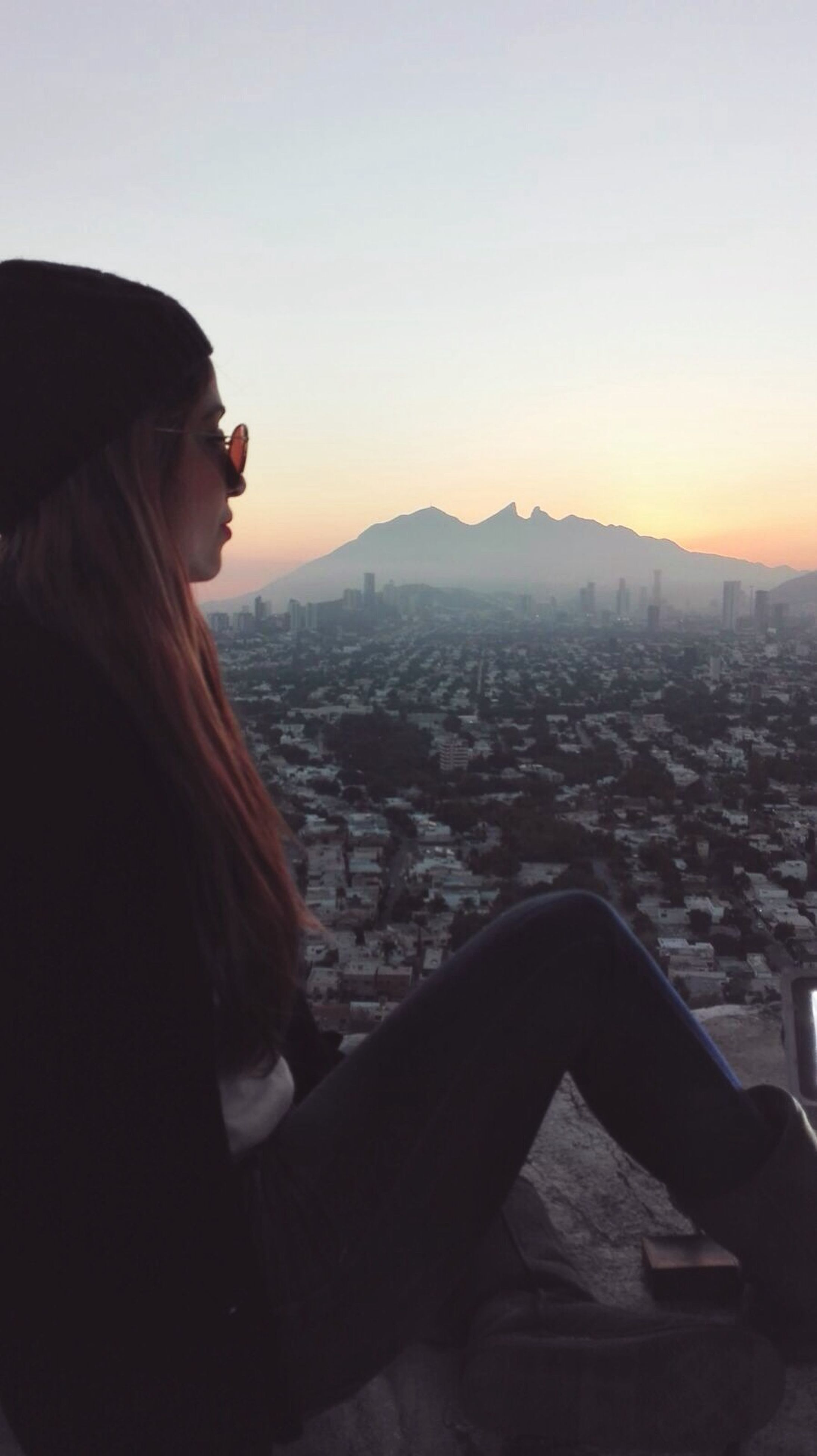 lifestyles, cityscape, leisure activity, mountain, sunset, building exterior, clear sky, architecture, city, built structure, young adult, copy space, looking at view, sky, casual clothing, waist up, landscape, sitting