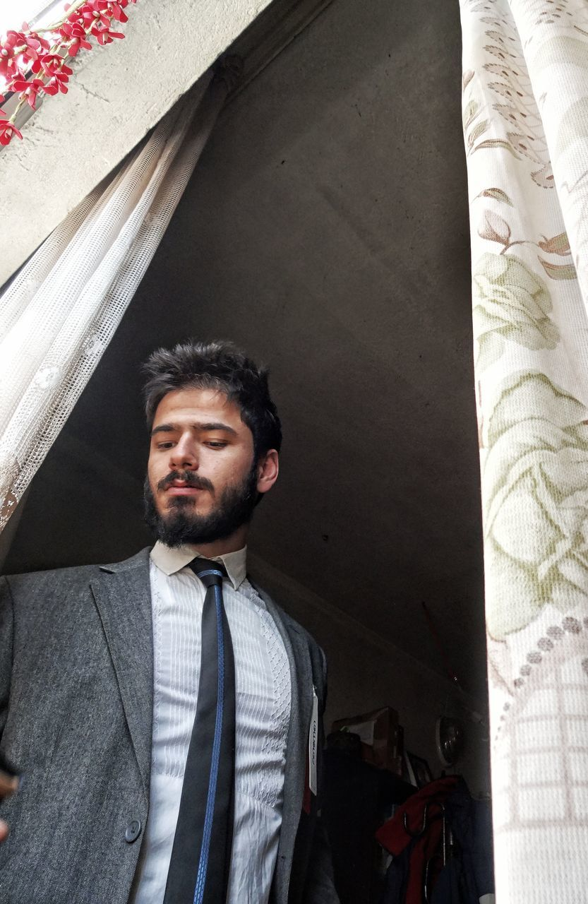 Low Angle View Of Young Businessman Standing At Window