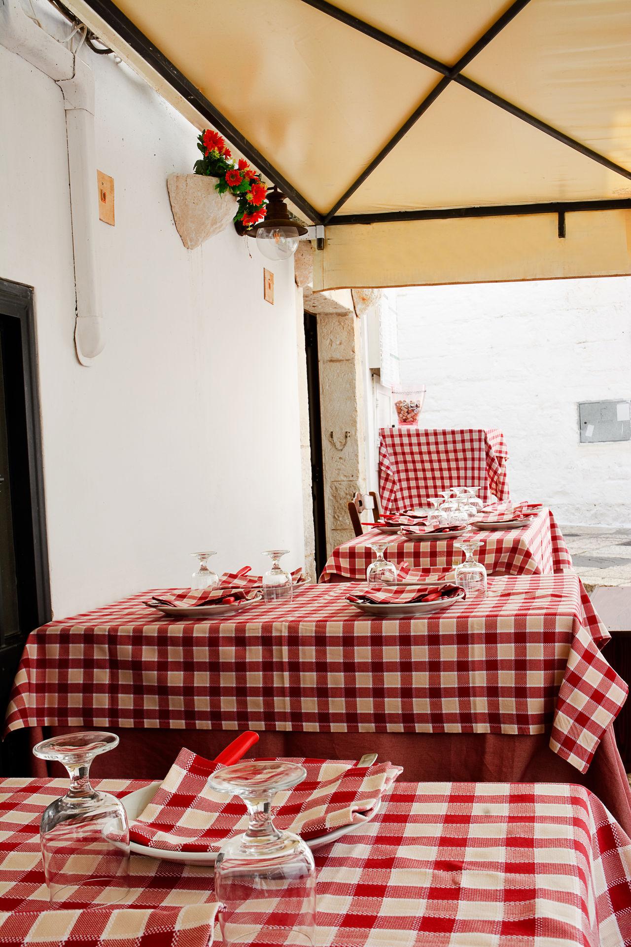 Table set in the alley of Cisternino (Apulia) Alley Apúlia Cisternino Cooker Dining Dinner Gazebo Glass Glasses Italy Itria Menu Napkin Ostuni Puglia Ready-to-eat Salento Set Table Tablecloth Tableware