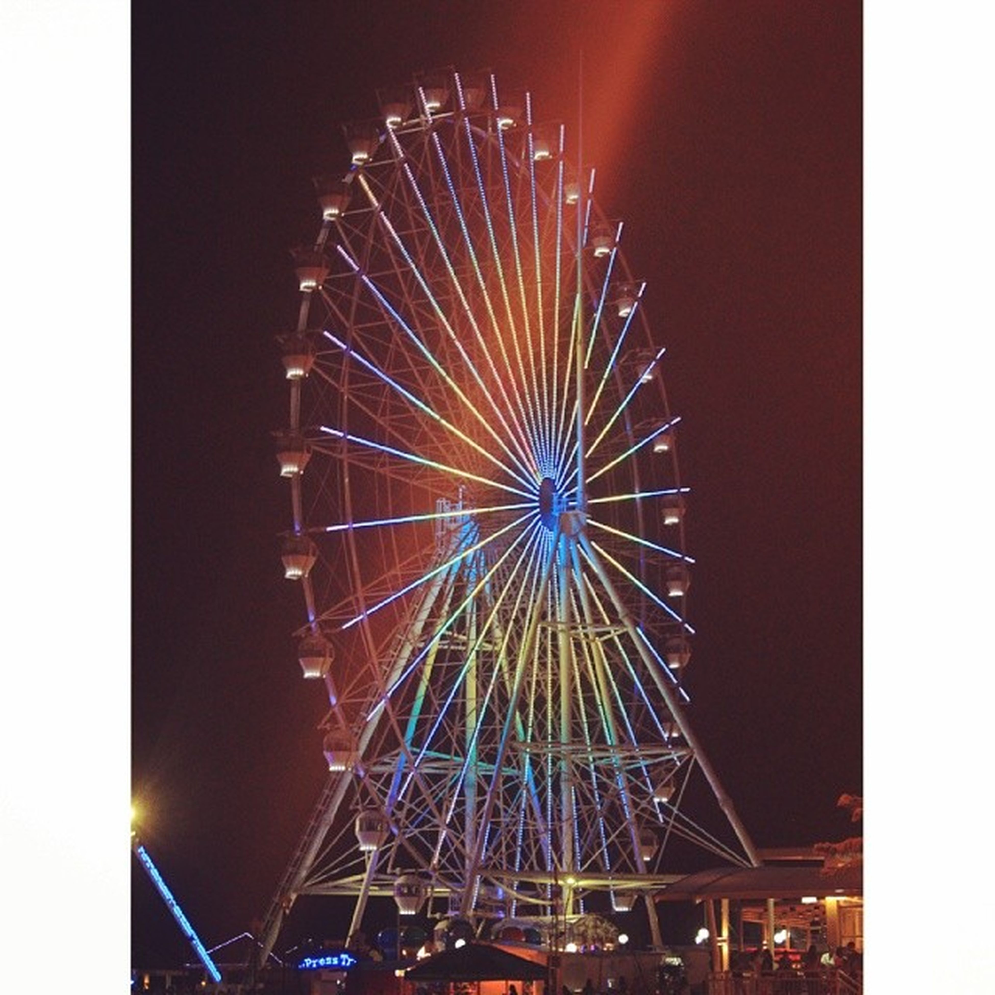 arts culture and entertainment, illuminated, night, ferris wheel, amusement park, amusement park ride, low angle view, sky, firework display, built structure, motion, multi colored, architecture, firework - man made object, glowing, exploding, long exposure, celebration, clear sky, transfer print