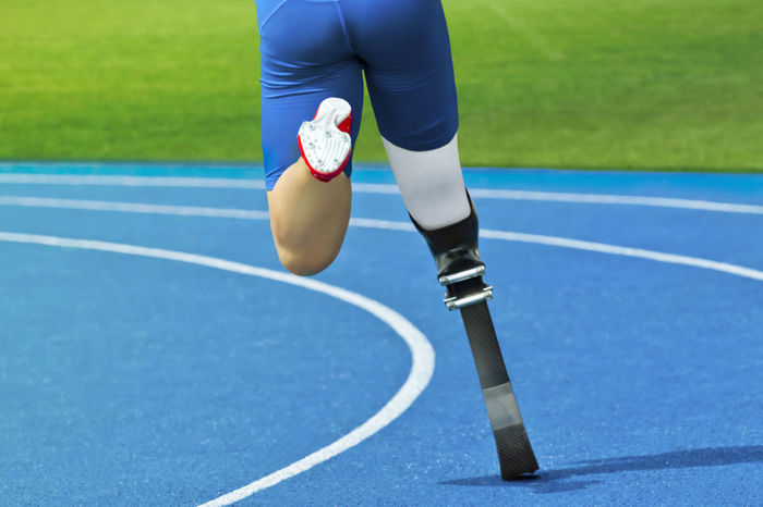 Rear view of handicapped track and field athlete Activity Amputation Athlete Competition Competitive Sport Court Day Exercising Handicapped Human Body Part Human Leg Lifestyles Low Section One Person Outdoors Professional Sport Prosthesis Real People Skill  Sport Sportsman Track And Field Women