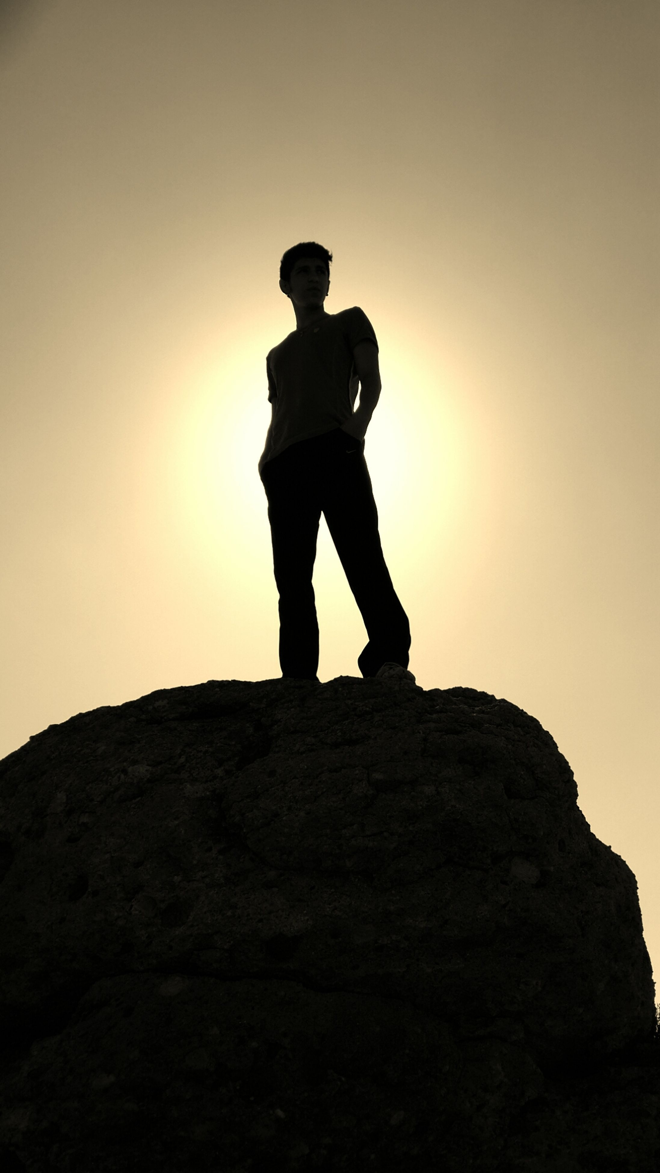 full length, silhouette, lifestyles, sunset, standing, leisure activity, sun, copy space, clear sky, low angle view, sky, men, rock - object, sunlight, tranquility, arms outstretched, casual clothing, nature