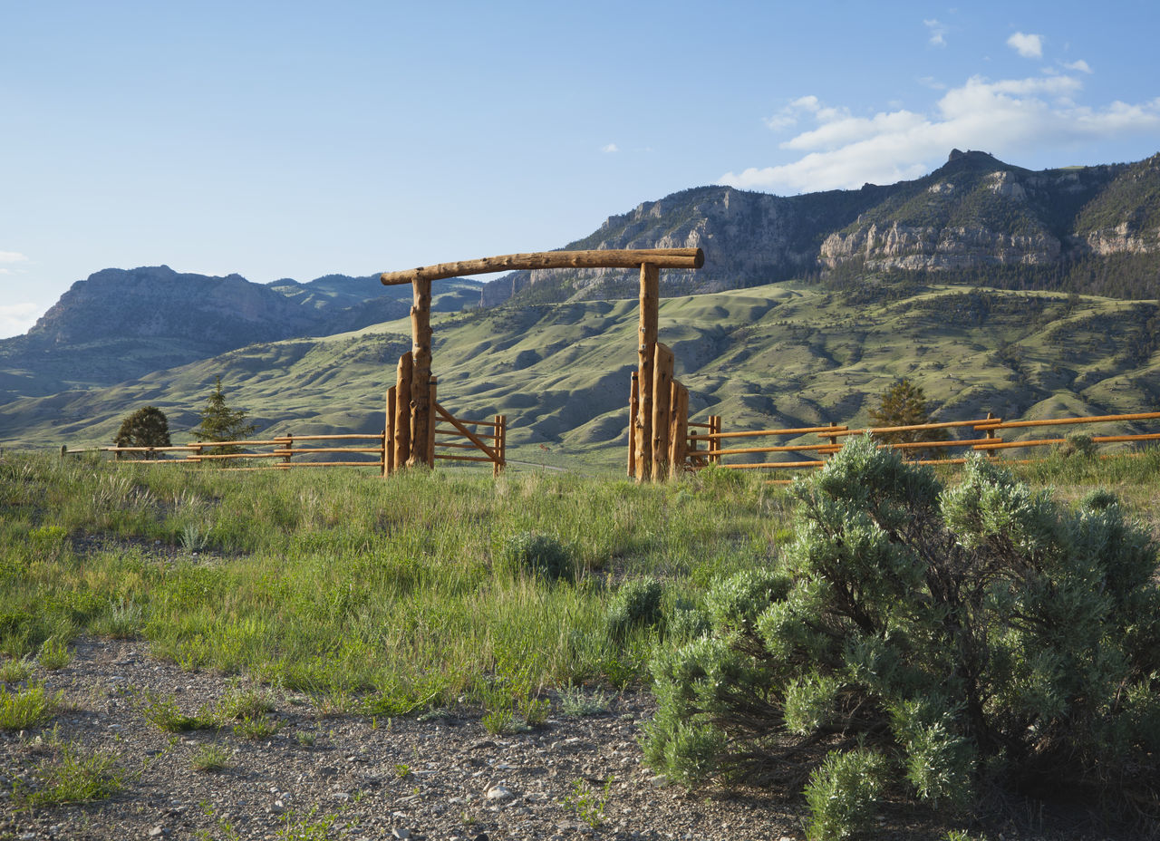 Ranch gate below cliffs of the Absaroka mountains in Wyoming Absaroka Blue Blue Sky Cliffs Clouds Day Fence Gate Grass Green Color Landscape Low Angle View Morning Mountain Mountain Range Nature No People Orange Ranch Sagebrush Scenics Sunlight USA West Wyoming