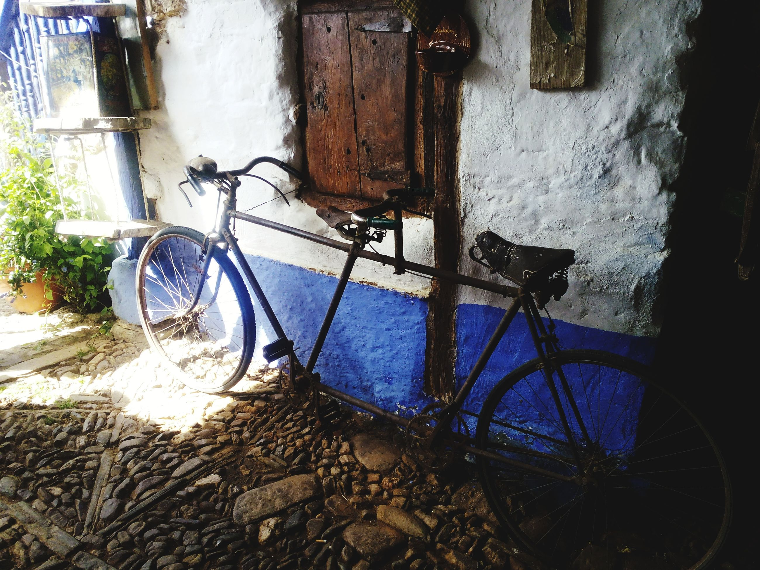 bicycle, mode of transport, built structure, transportation, parked, architecture, stationary, building exterior, parking, land vehicle, metal, wall - building feature, abandoned, old, day, water, no people, sunlight, house, absence
