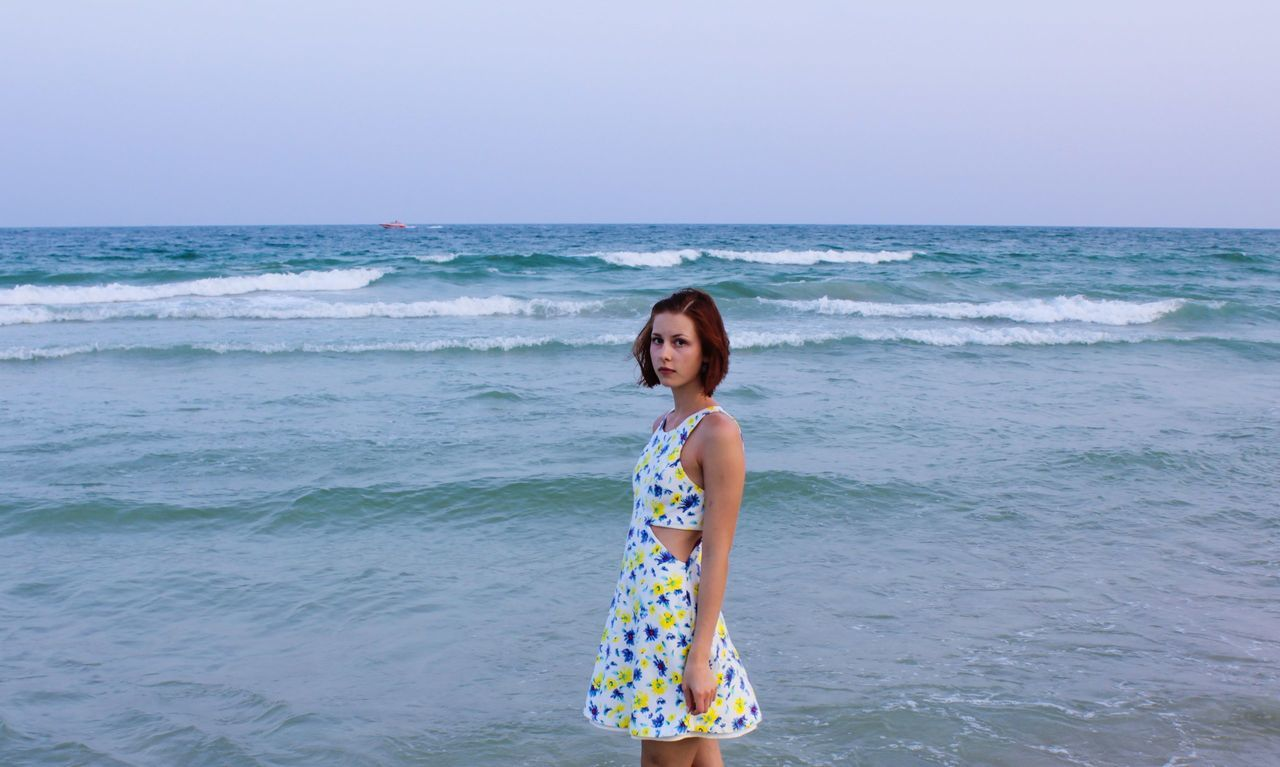 Portrait Of Young Woman Standing At Seashore Against Clear Sky