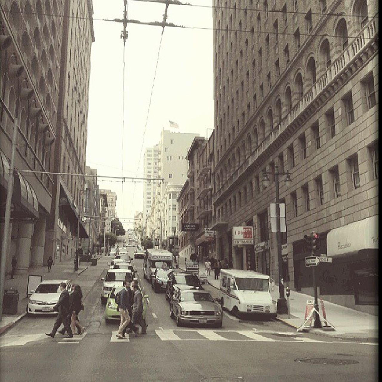 city, street, architecture, transportation, road, building exterior, city life, car, land vehicle, built structure, real people, mode of transport, walking, day, outdoors, men, skyscraper, electricity pylon, sky, cityscape, adult, people