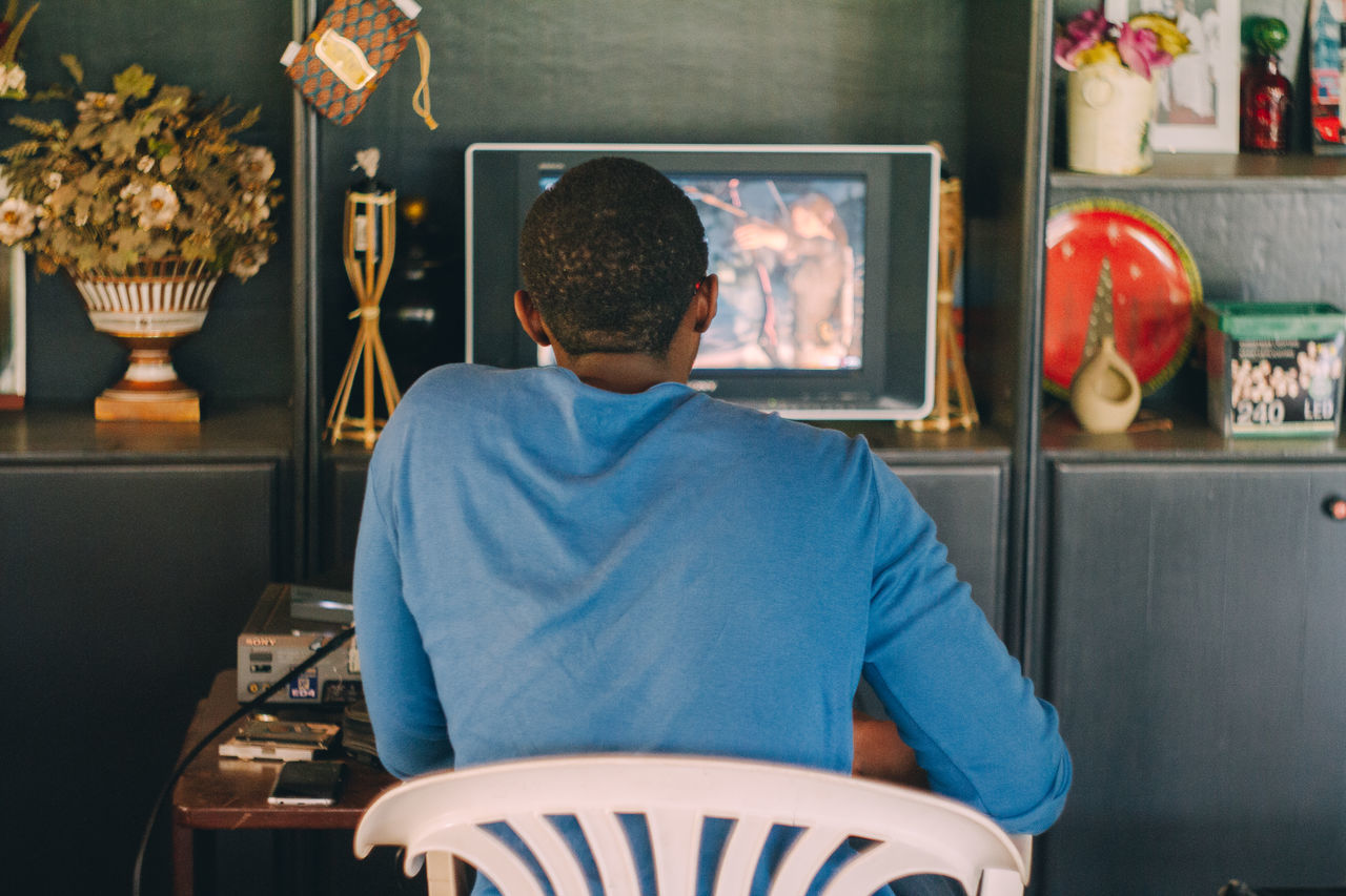 blue shirt corner shop indoors one man only playing video games Rear view technology watching television