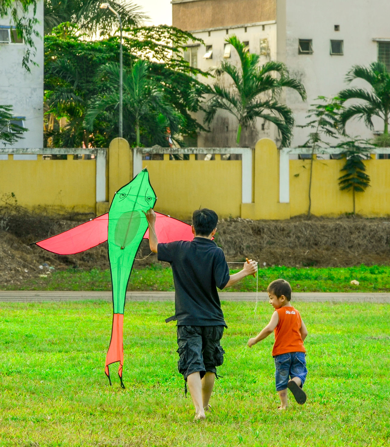 Childhood kite Casual Clothing Day Father Father & Son Full Length Grass Green Color Kite Lawn Leisure Activity Lifestyles Nature Outdoors Son The Street Photographer – 2016 EyeEm Awards