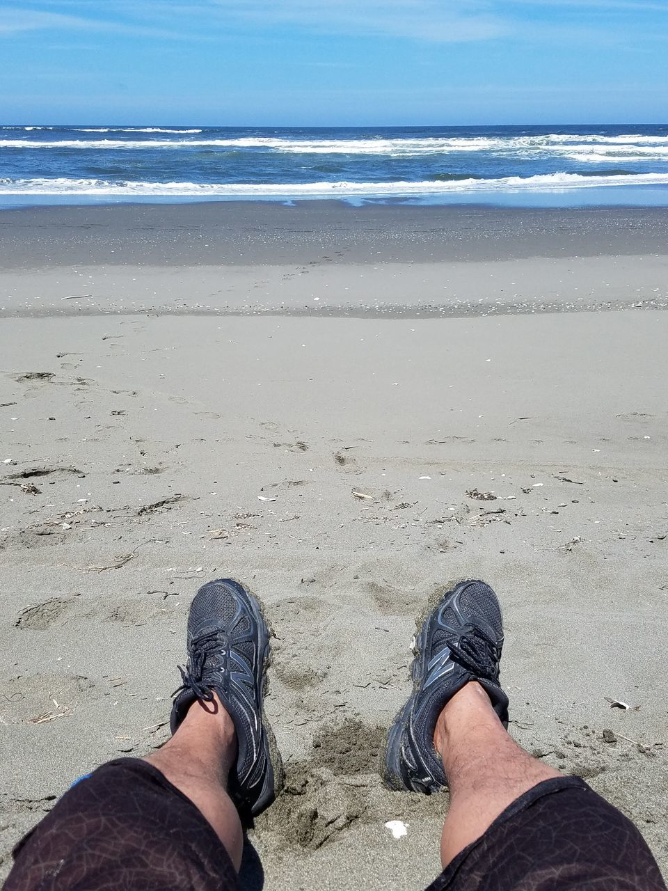 human leg, low section, beach, shoe, human body part, one person, personal perspective, real people, day, sea, men, standing, high angle view, leisure activity, sand, lifestyles, outdoors, nature, one man only, horizon over water, sky, water, close-up, only men, adult, people, adults only