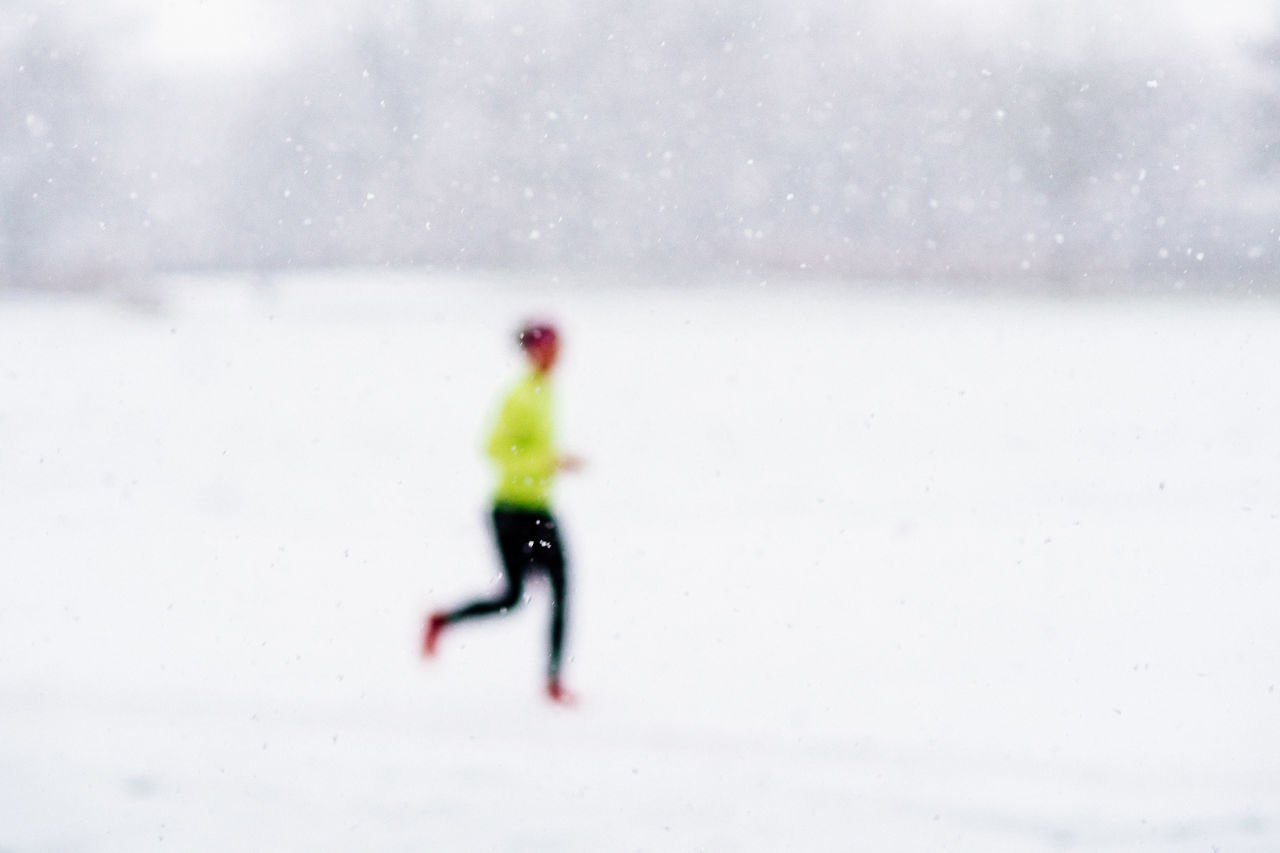 Defocused Image Of Person Running On Snowfield