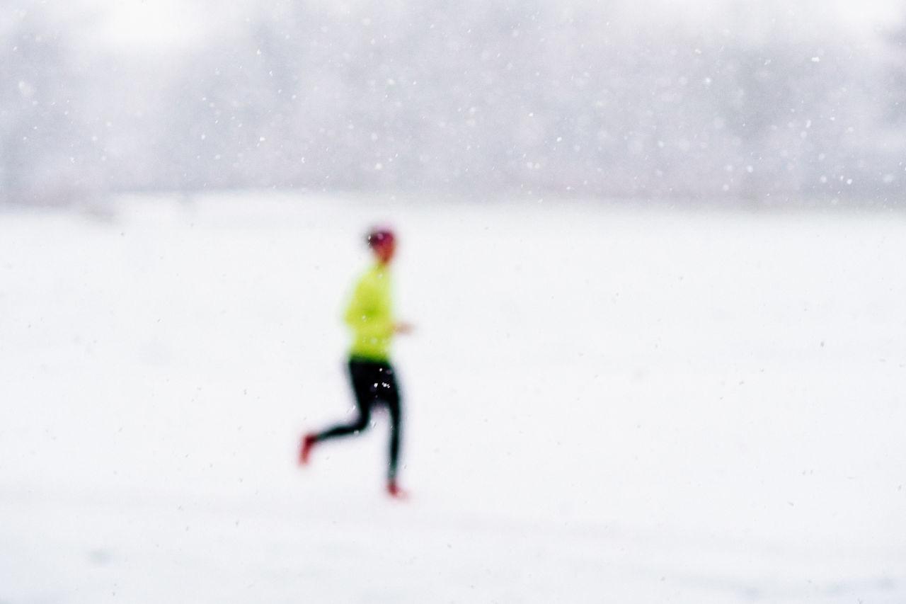 Defocused Image Of Person Running On Snowfield