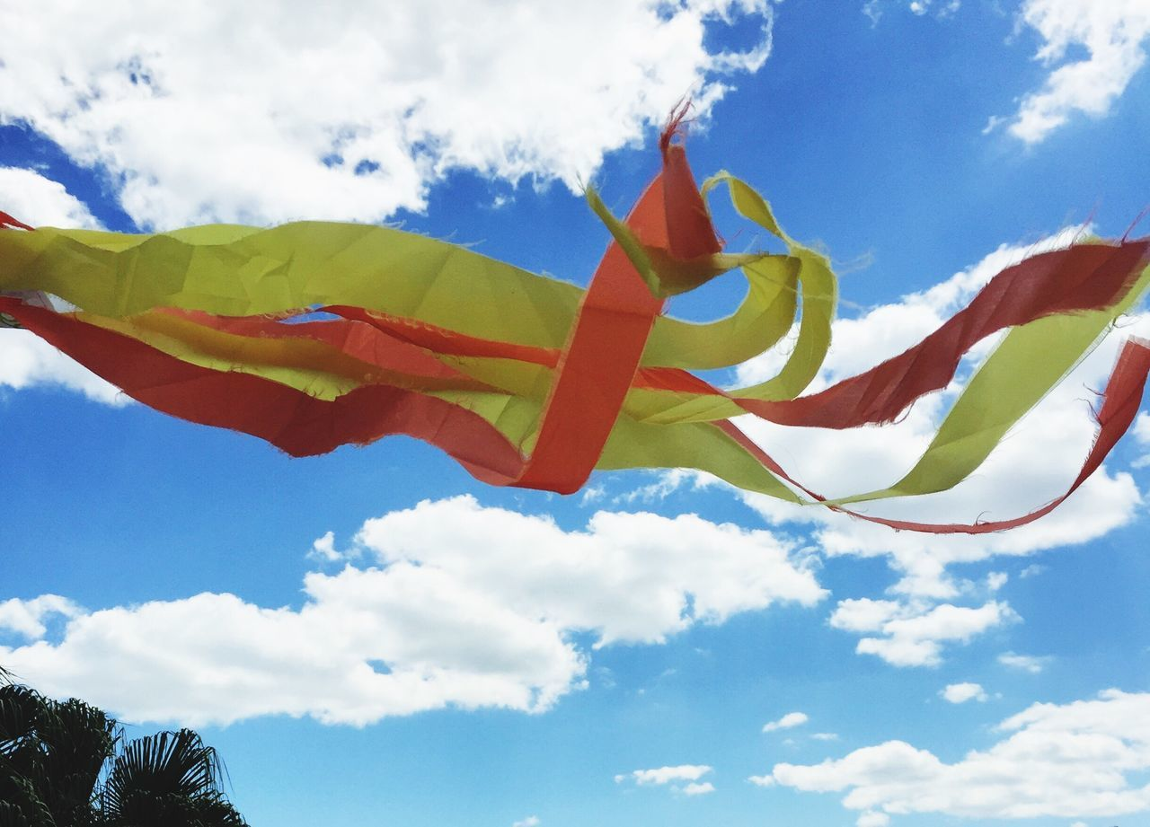 sky, cloud - sky, low angle view, flag, day, blue, outdoors, wind, multi colored, no people, beauty in nature, nature