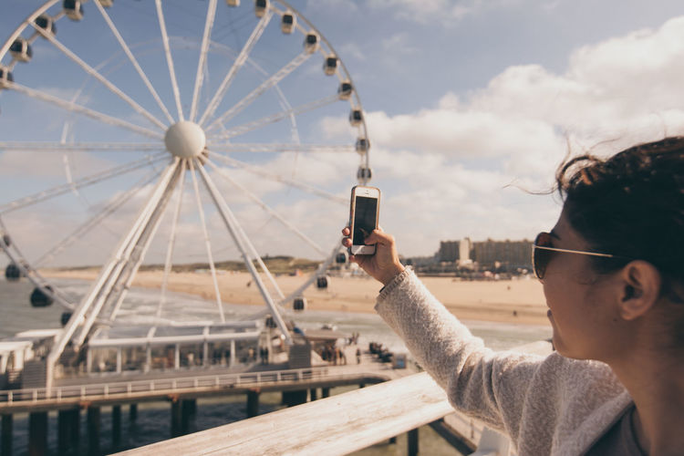Netherlands Photographing The Photographer Rear View Scheveningen  Woman Amusement Park Architecture Beach Built Structure Close-up Day Ferris Wheel Holding In Hand Leisure Activity One Person Outdoors Photographing Real People Side View Sky Smart Phone Tourism Using Phone Wireless Technology