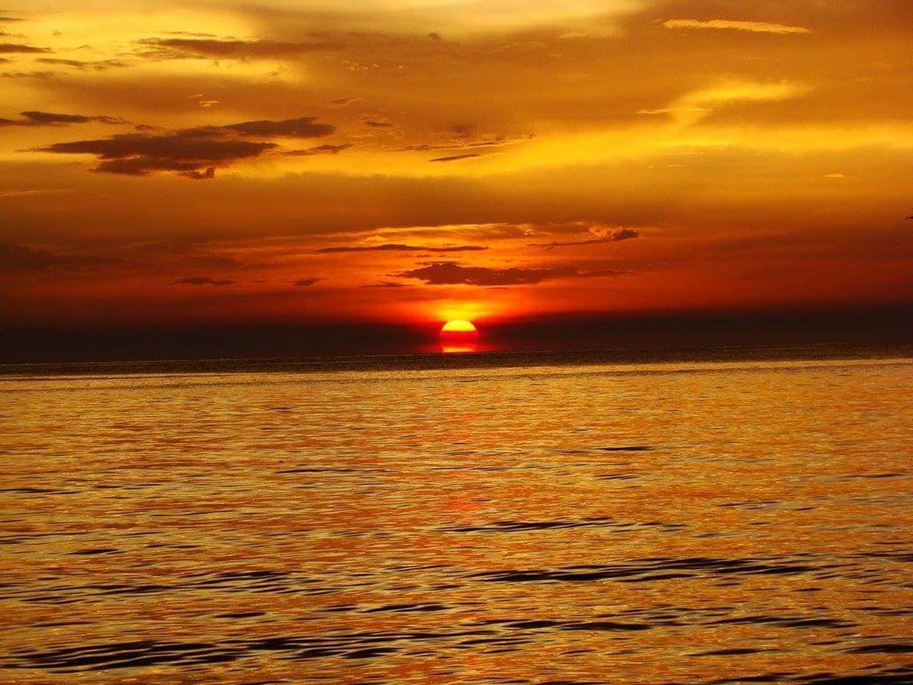sunset, orange color, beauty in nature, sea, scenics, nature, dramatic sky, sun, horizon over water, cloud - sky, majestic, tranquility, tranquil scene, sky, atmospheric mood, no people, outdoors, idyllic, vibrant color, reflection, silhouette, red, awe, water, travel destinations, multi colored, horizon, wave, day