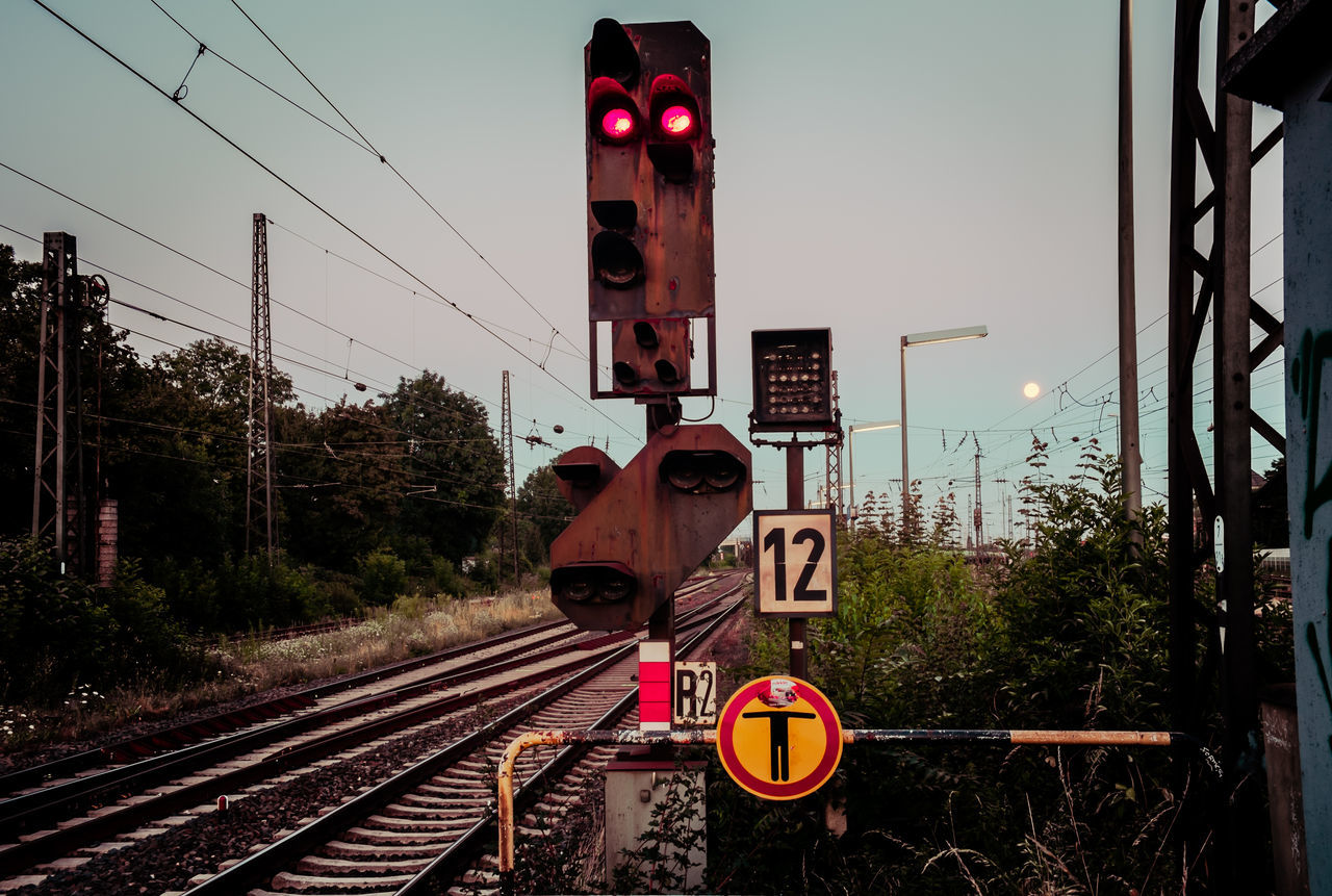 transportation, communication, railway signal, railroad crossing, rail transportation, railroad track, guidance, warning sign, crossing sign, safety, red light, sky, road sign, tree, stoplight, public transportation, no people, day, outdoors, clear sky, electricity pylon