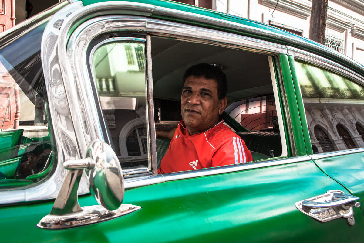 A taxi driver waits for clients on his green vintage car in Cienfuegos, Cuba. Car Cienfuegos Cienfuegos, Cuba City Life Cuba Cuba Collection Cuban Mode Of Transport People Person Portrait Transportation Travel Travel Destinations Traveling Vintage Car