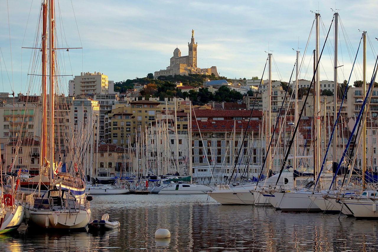 View from the old port to the Basilica Notre-Dame-de-la-Garde in Marseille, Farnce. Architecture Basilica Notre-Dame-de-la-Garde Boat Building Exterior Built Structure City Cloud - Sky Harbor Mast Mode Of Transport Nautical Vessel Old Port Outdoors Sea Sky Transportation Water Waterfront