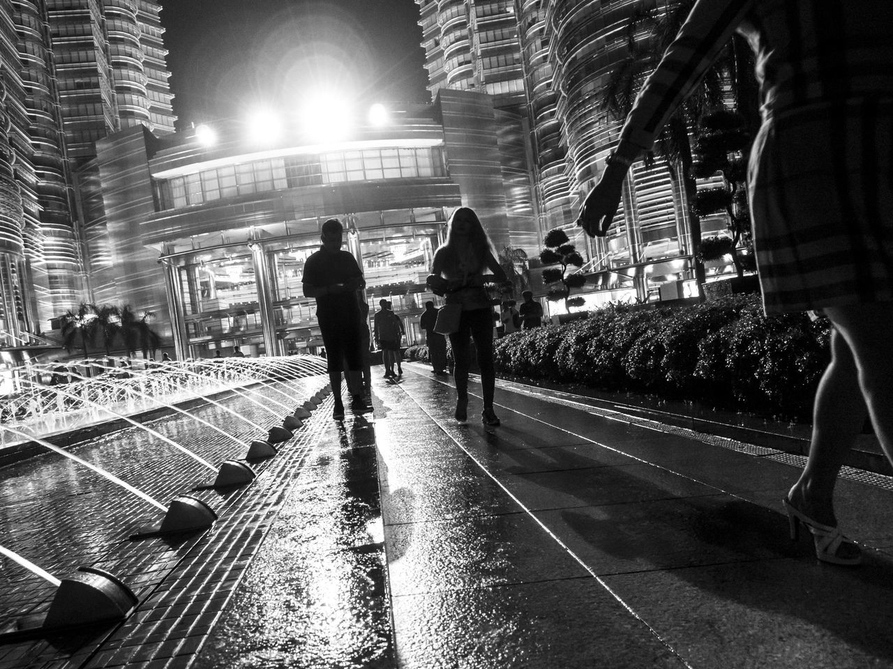 Silhouettes of people on a wet ground with a small fountain on one side and a modern building at the back After The Rain Architecture B&w B&w Photography Black And White Blackandwhite City City Life City Lights Cityscape Illuminated Lights Night Nightphotography Outdoors Petronas Twin Towers Silhouette Silhouettes Streetphotography Togetherness Urban Urbanphotography Walk This Way Walking Wet