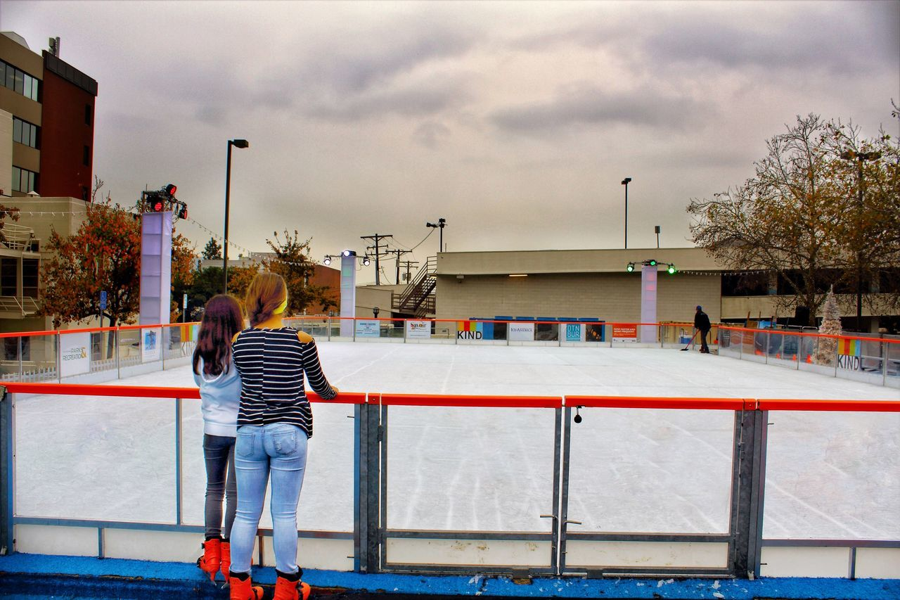 real people, leisure activity, architecture, built structure, sport, one person, playing, lifestyles, full length, cloud - sky, sky, day, building exterior, outdoors, ice rink, people