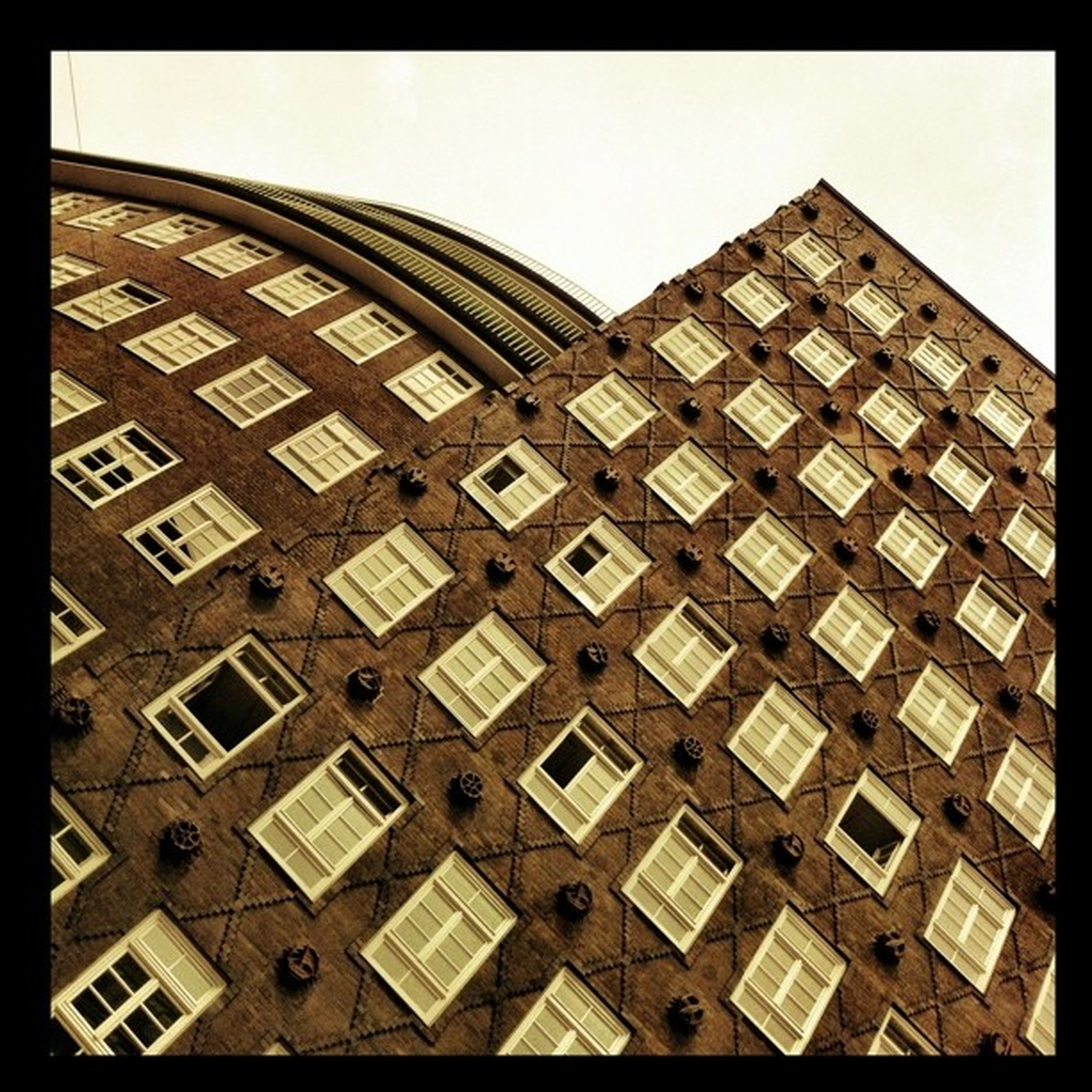 transfer print, architecture, built structure, building exterior, auto post production filter, low angle view, pattern, window, repetition, building, geometric shape, architectural feature, in a row, clear sky, full frame, no people, day, city, design, brick wall