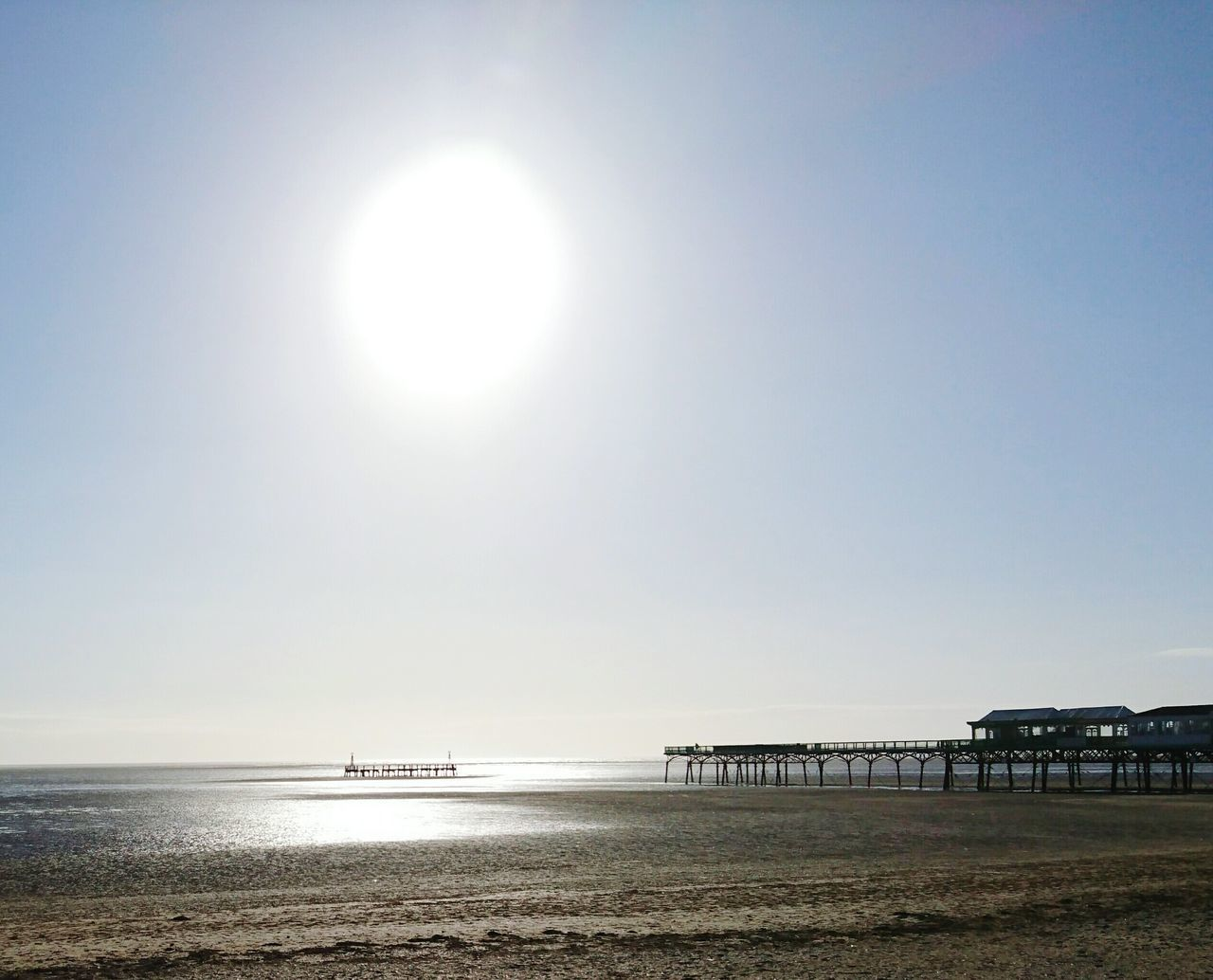 sun, sunlight, sea, water, lens flare, beach, sunny, day, nature, tranquility, outdoors, built structure, scenics, clear sky, bright, beauty in nature, tranquil scene, horizon over water, sand, sky, no people, architecture, travel destinations