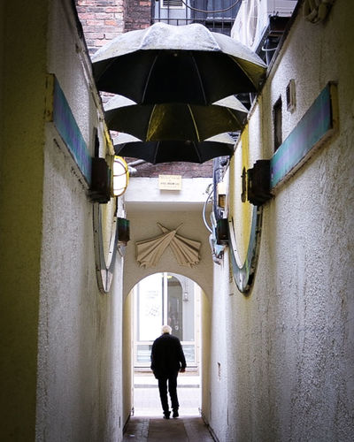 Alley Architecture Building Exterior Built Structure Day Full Length Men Narrow Outdoors Person Rear View Standing The Way Forward Umbrella Umbrella Revolution Perspectives On Nature