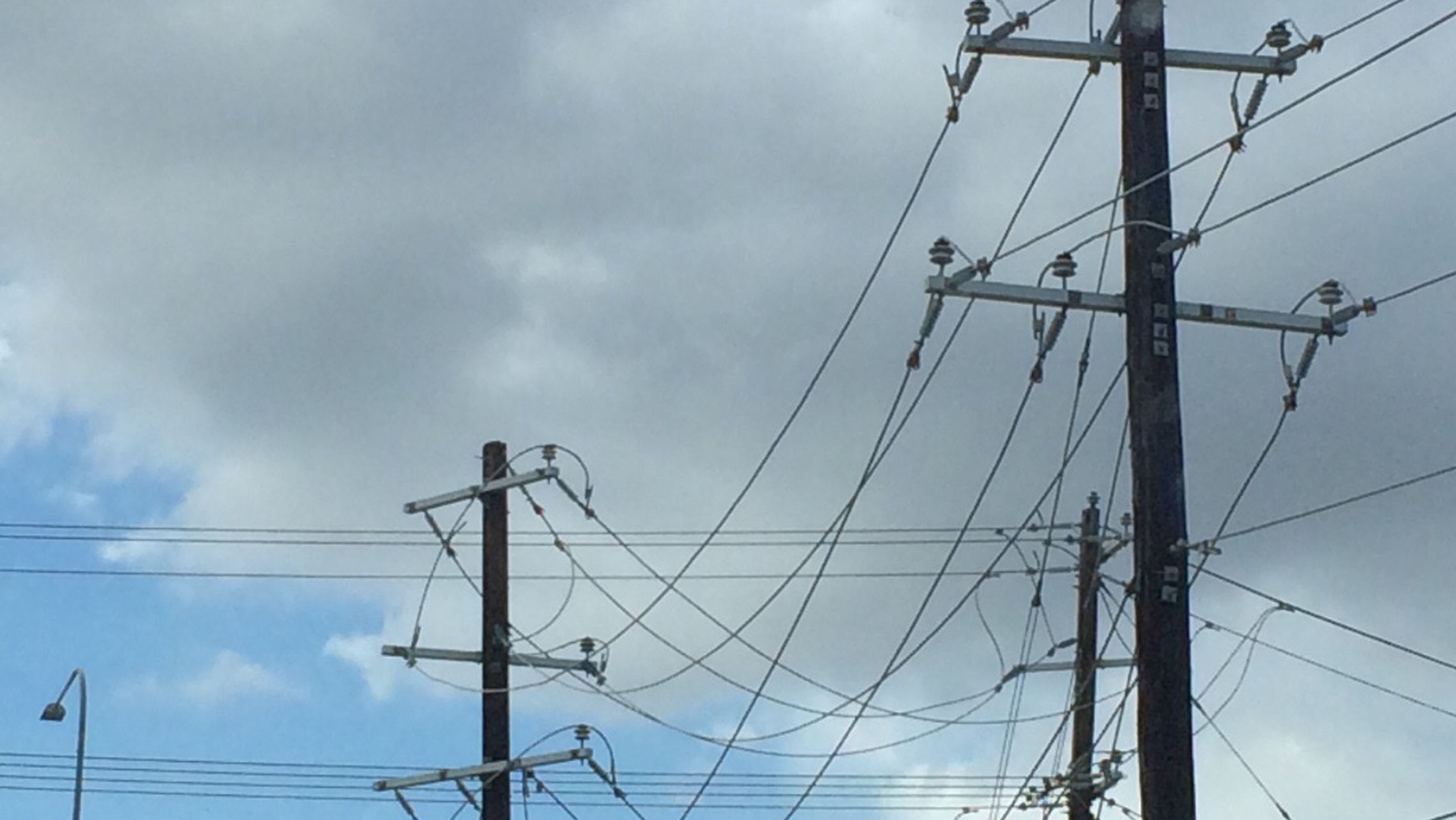 electricity pylon, electricity, power line, connection, power supply, low angle view, cable, technology, fuel and power generation, sky, cloud, high section, day, power cable, pole, electricity tower, outdoors, telephone line, nature, pylon, telephone pole, cloud - sky, no people, tranquility, outline, cloudscape, tall