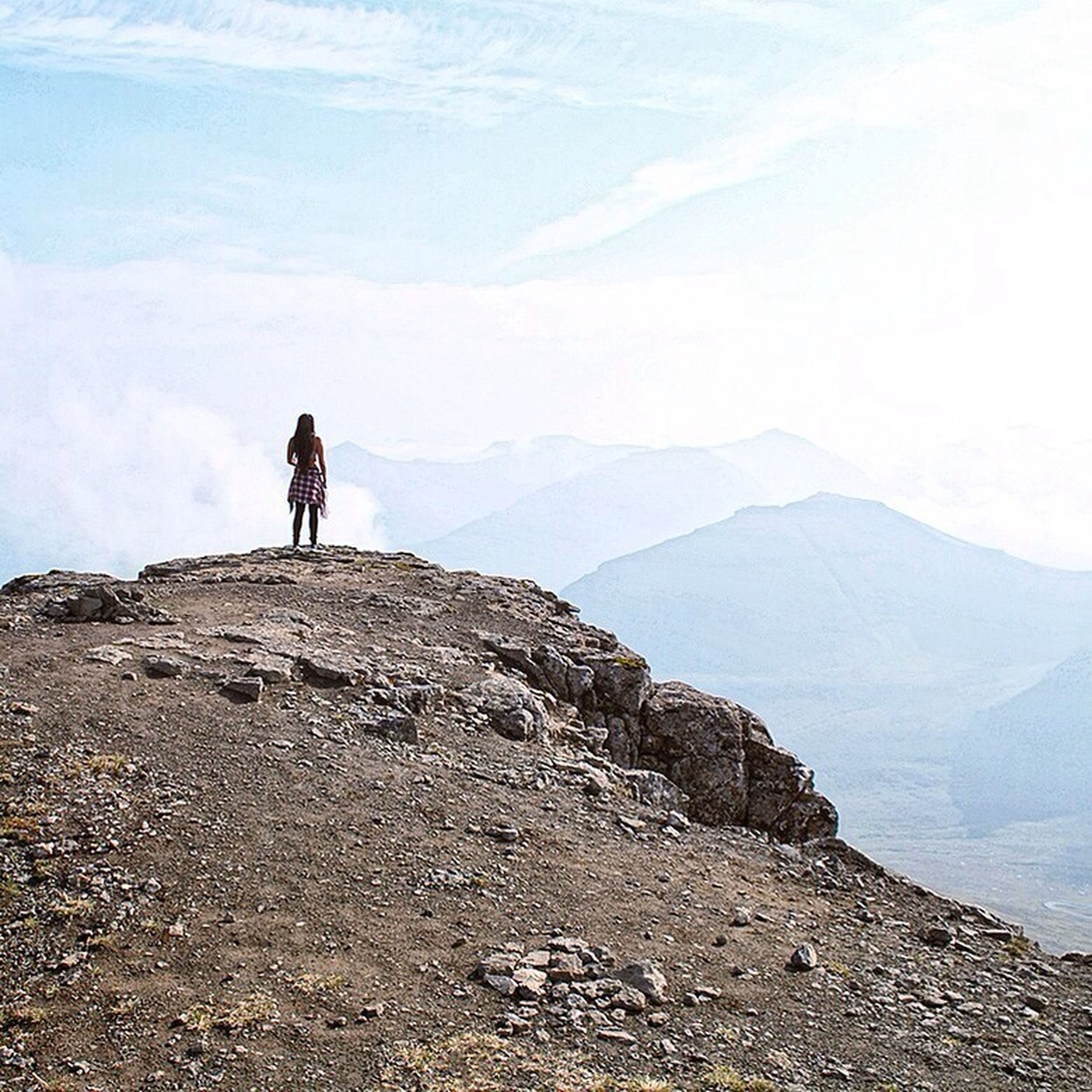 lifestyles, leisure activity, mountain, men, standing, full length, sky, hiking, tranquility, tranquil scene, rear view, scenics, nature, beauty in nature, rock - object, looking at view, mountain range, landscape